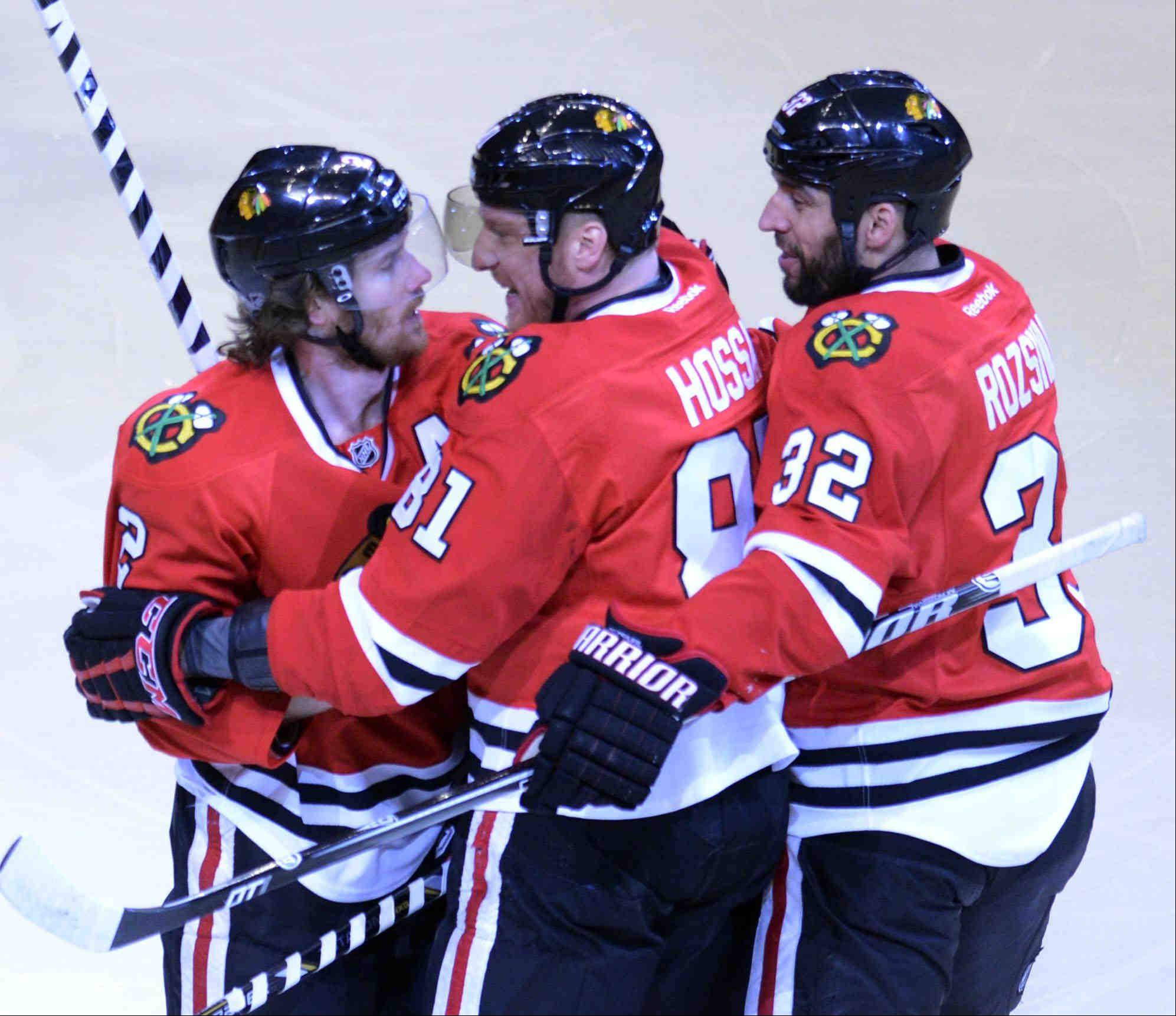 John Starks/jstarks@dailyherald.comChicago Blackhawks defenseman Duncan Keith is congratulated by teammates Marian Hossa and Michal Rozsival after his first period goal against the Los Angeles Kings Saturday during the NHL Western Conference Finals Game 5 at the United Center in Chicago.
