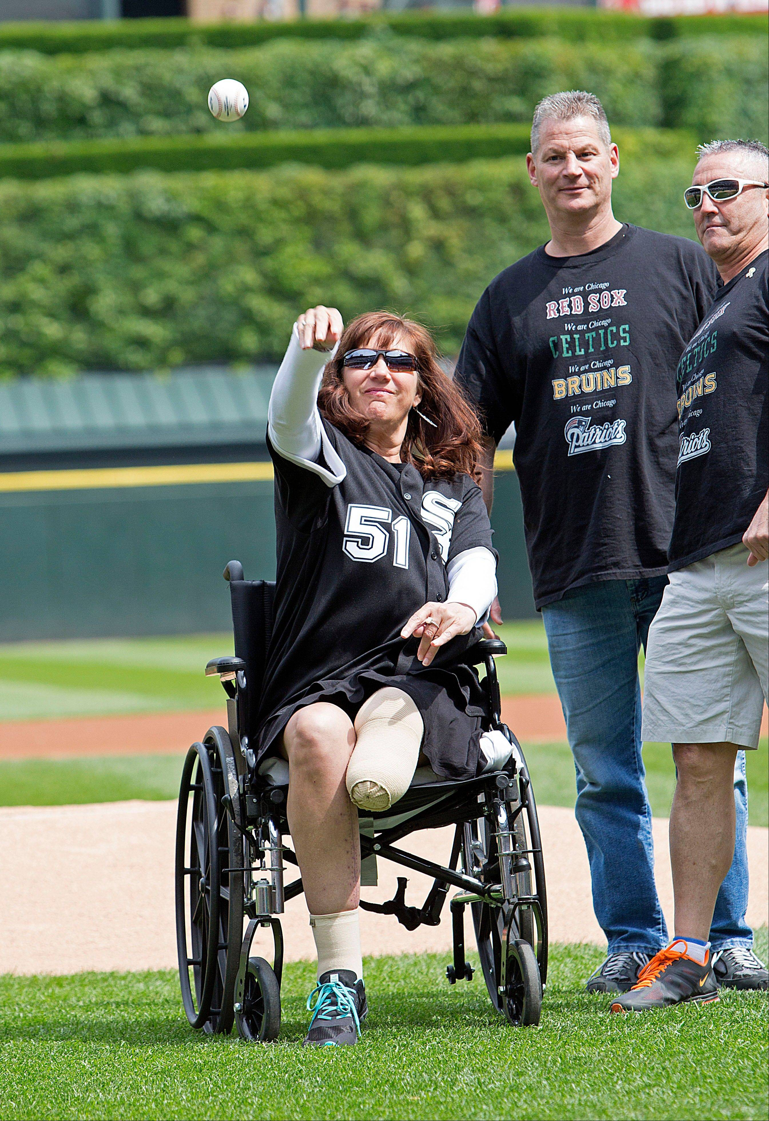 Karen Rand, who lost part of her leg in the Boston Marathon bomb blasts, throws out the ceremonial first pitch before Saturday's game between the White Sox and Athletics at U.s. Cellular Field.