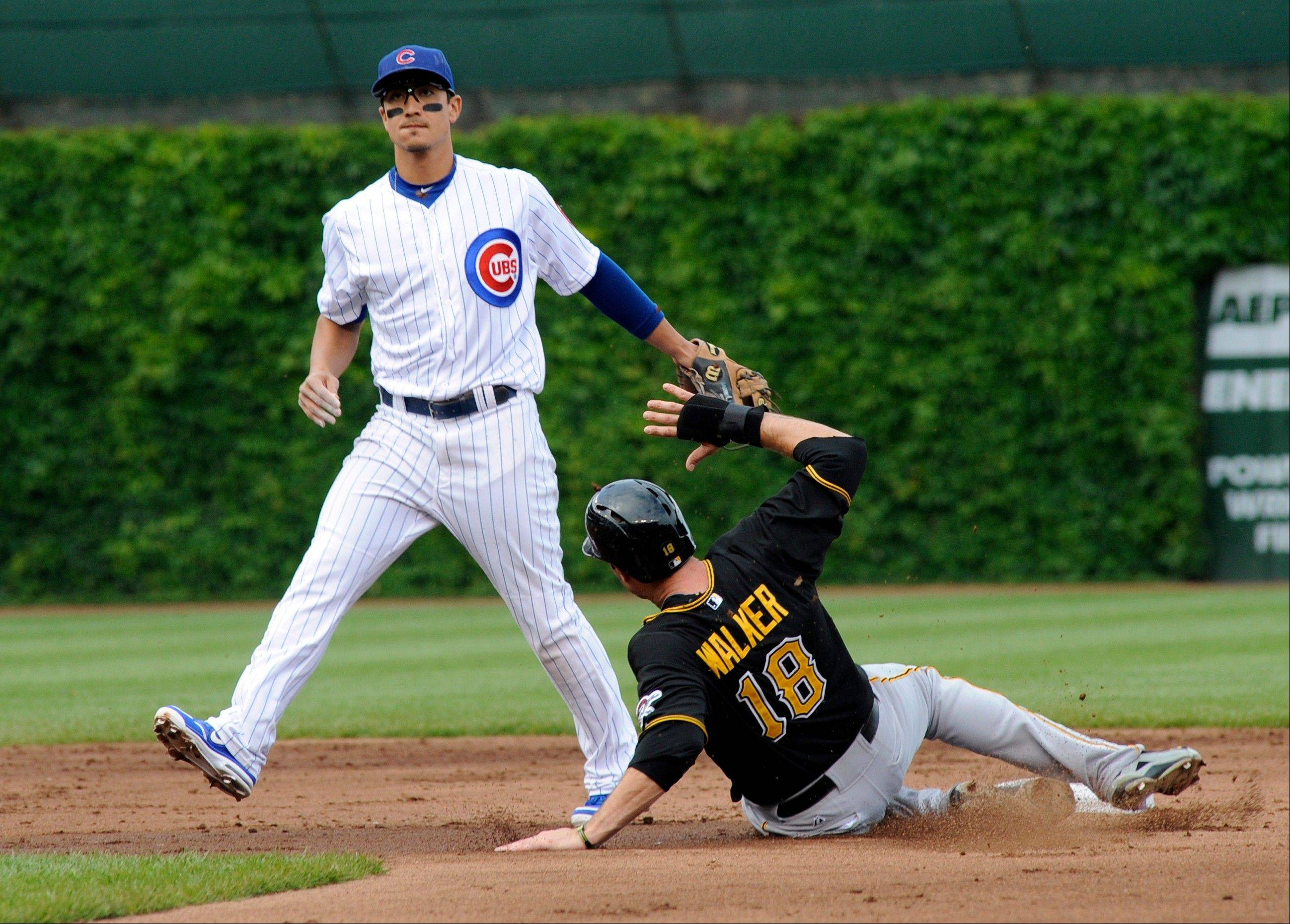 Pittsburgh Pirates' Neil Walker, right, is out at second base after Chicago Cubs' Darwin Barney stepped on the base during a baseball game on Saturday June 8, 2013, in Chicago, Ill.