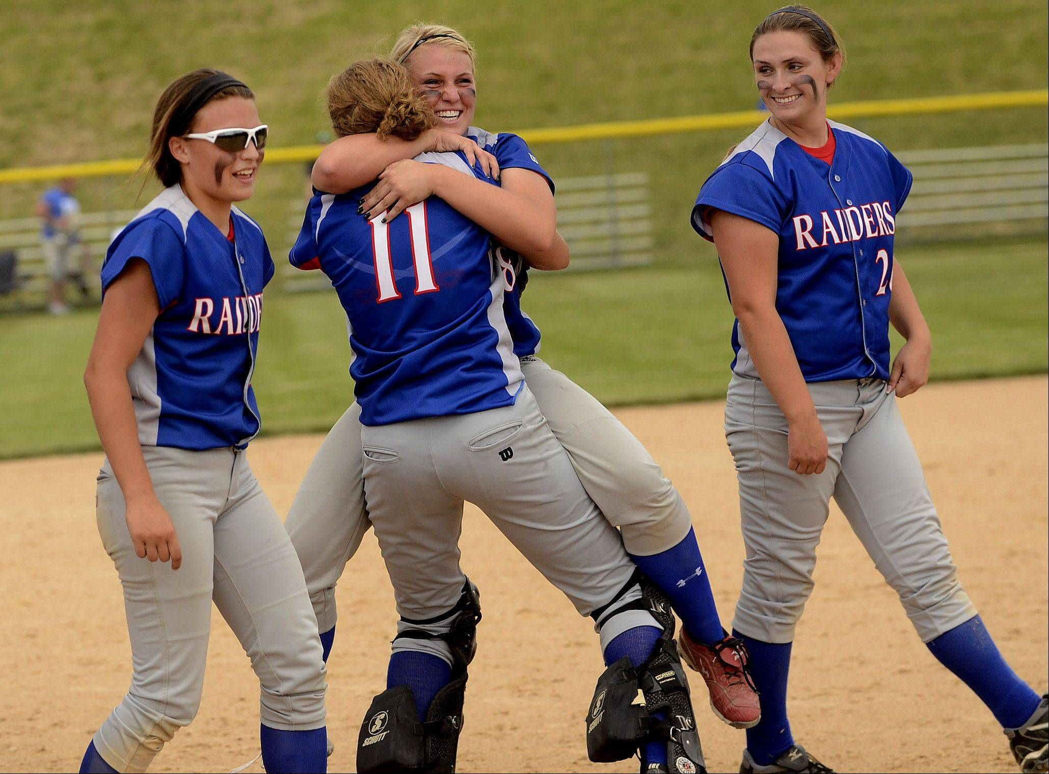 Catcher Jane Trzaska, left, and pitcher Stephanie Chitkowski embrace after the final out of the game, as Glenbard South repeats as Class 3A state champions after defeating Alton Marquette Saturday.