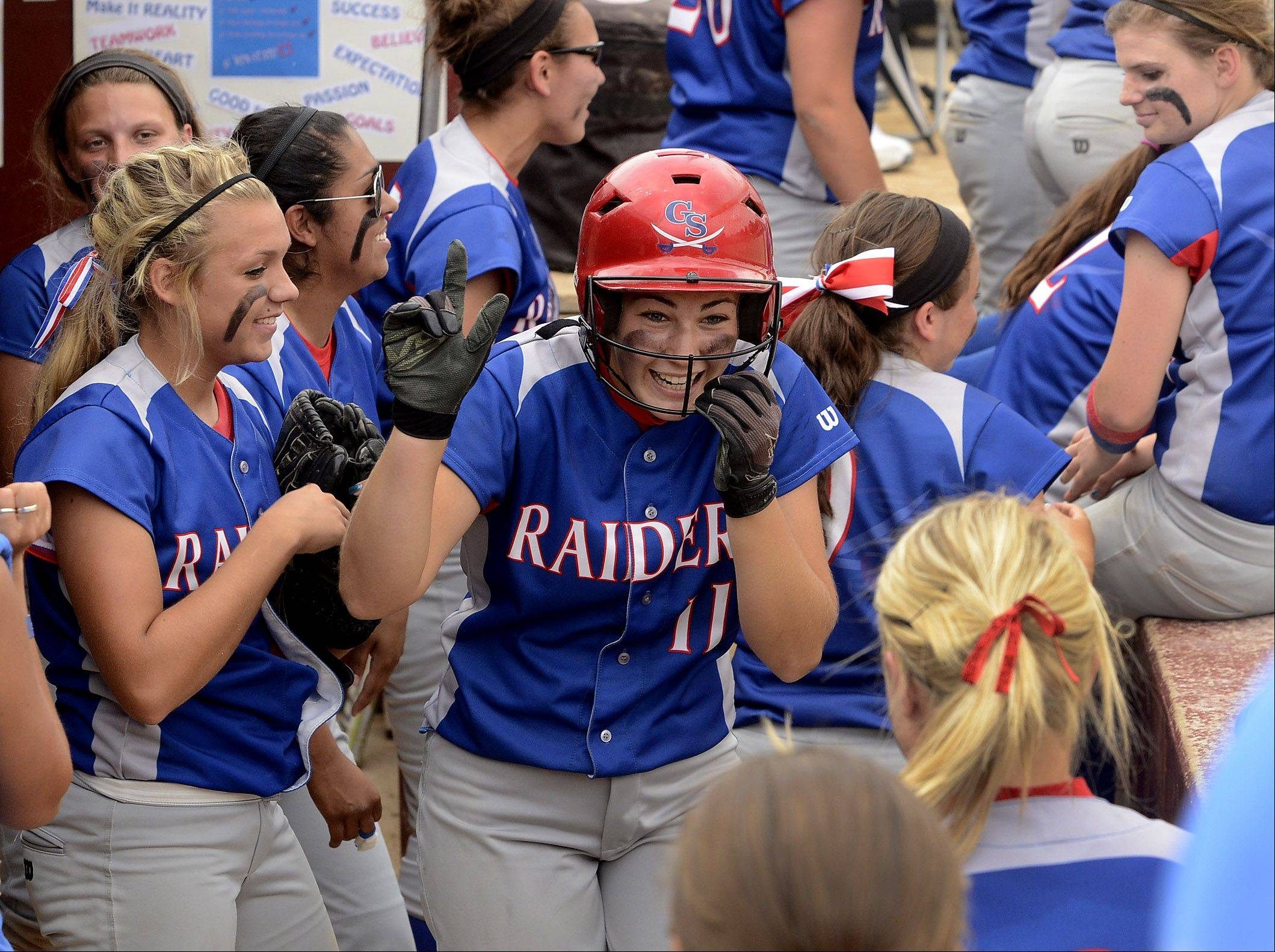 Glenbard South's Jane Trzaska celebrates with teammates in the dugout after tripling to right in the top of the seventh for the eventual game winning hit in the Class 3A state championship game between Glenbard South and Alton Marquette.