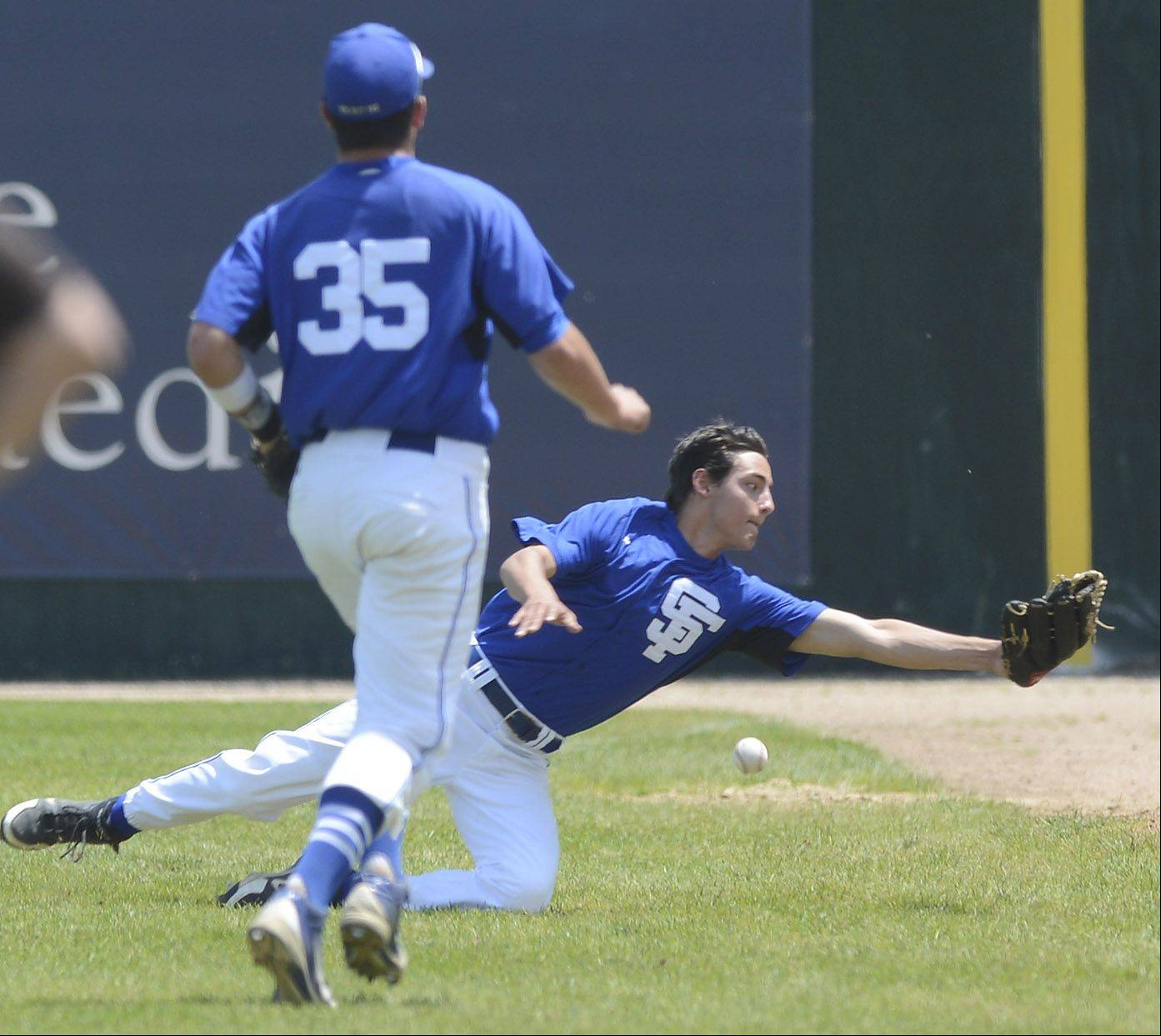 St. Francis right fielder Nick Dama makes a diving attempt on a foul ball as first baseman Josh Croci runs to help during the Class 3A state baseball championship game against Joliet Catholic at Silver Cross Field in Joliet Saturday.