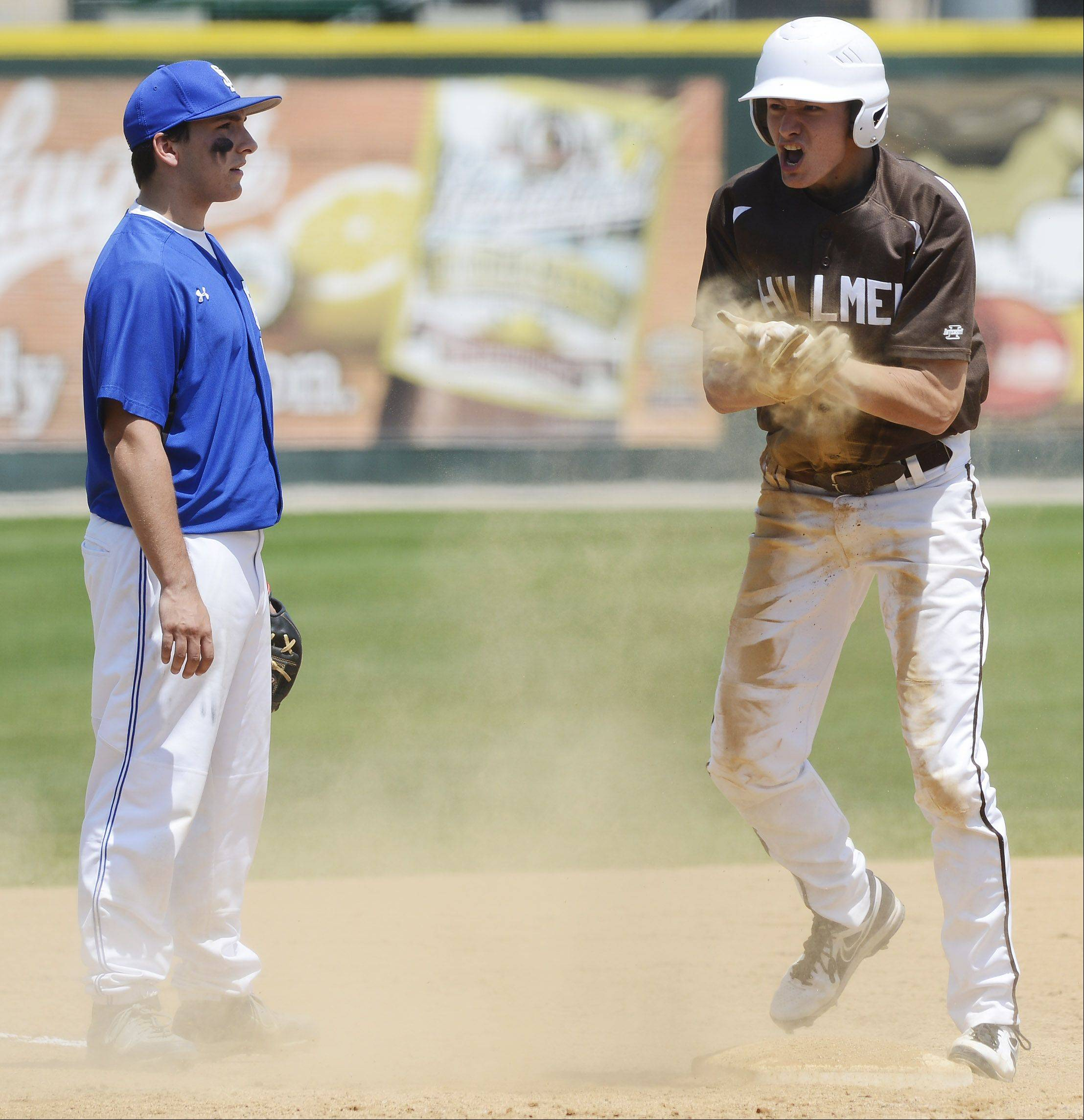 Joliet Catholic's John Kalisik celebrates his fourth inning triple as St. Francis third baseman Chris Smith stands beside the base during the Class 3A state baseball championship game at Silver Cross Field in Joliet Saturday.