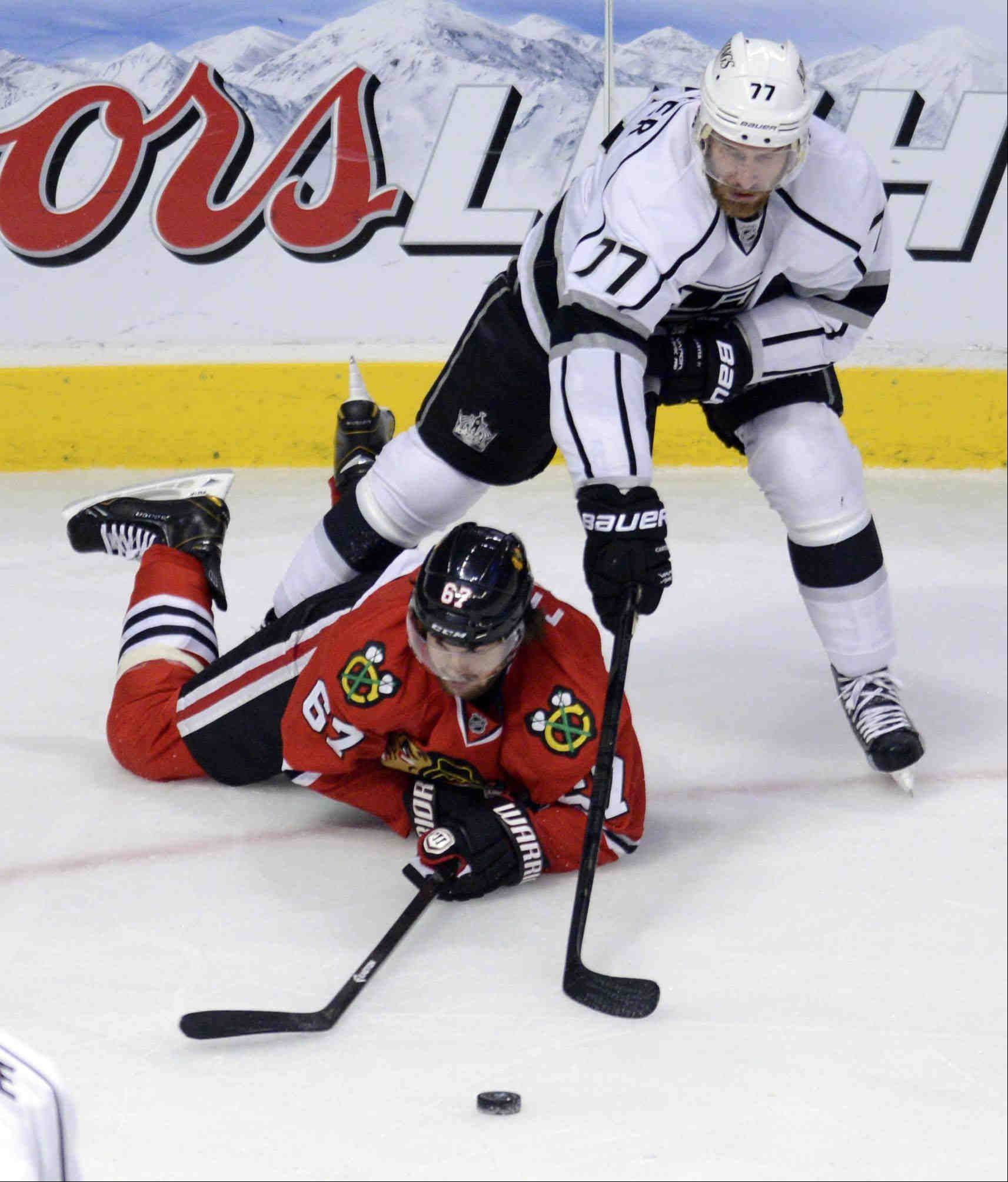Chicago Blackhawks center Michael Frolik tries to play from his stomach as Los Angeles Kings center Jeff Carter plays over him Saturday during the NHL Western Conference Finals Game 5 at the United Center in Chicago.