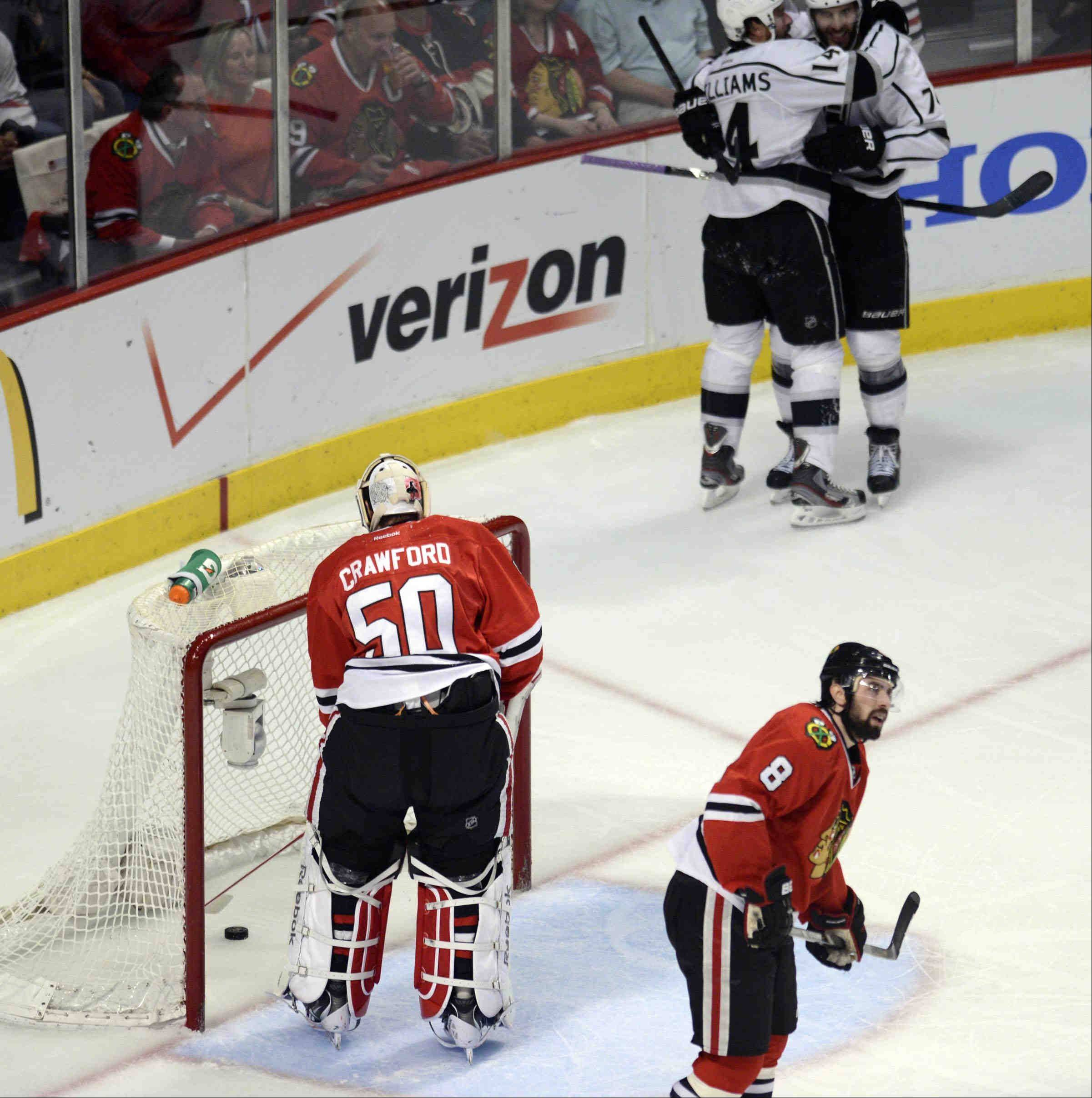 Chicago Blackhawks goalie Corey Crawford scoops the puck from his own net as Los Angeles Kings center Dwight King and Justin Williams celebrate King's short-handed goal in the second period Saturday during the NHL Western Conference Finals Game 5 at the United Center in Chicago.