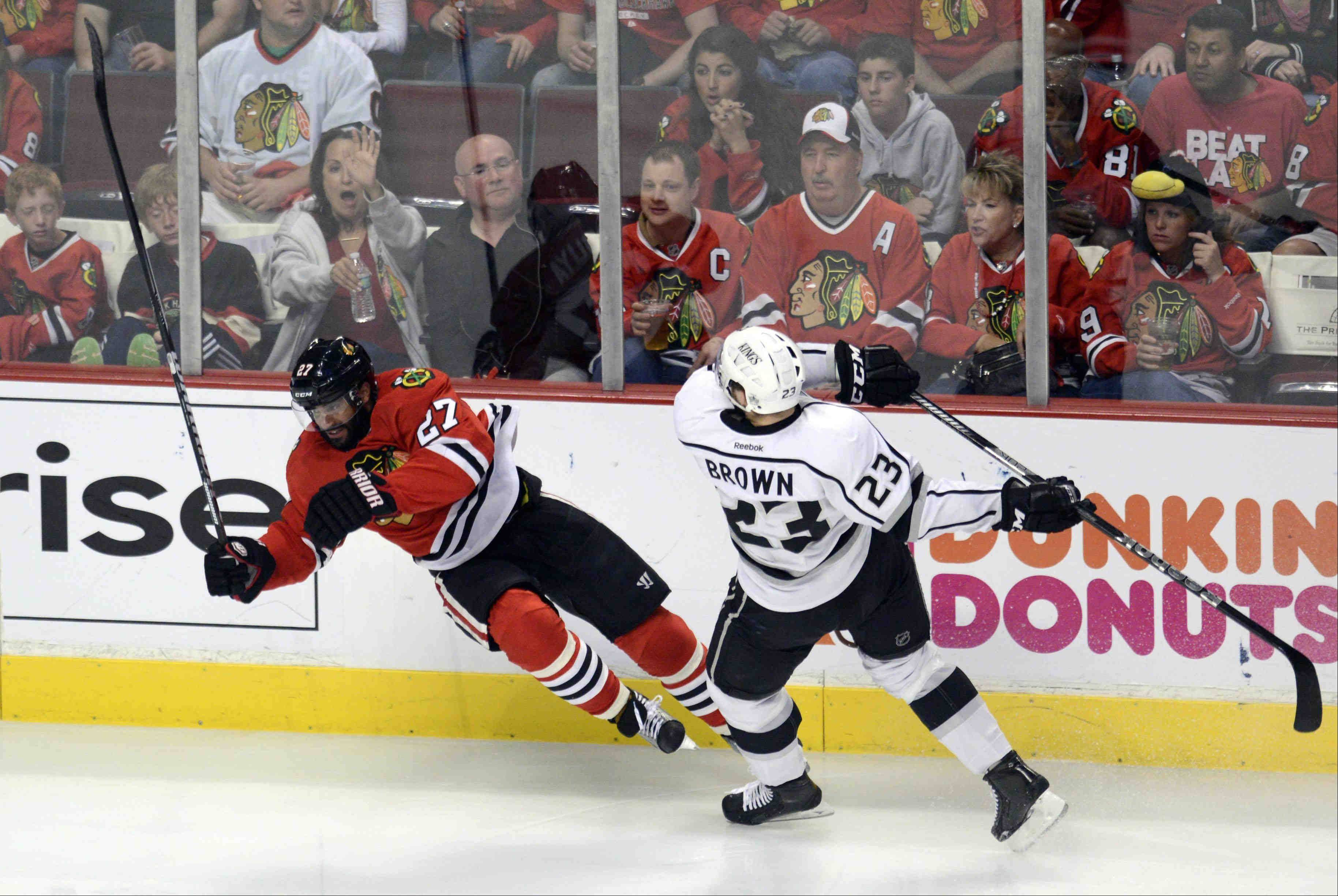 Chicago Blackhawks defenseman Johnny Oduya and Los Angeles Kings right wing Dustin Brown fall to the ice after colliding Saturday during the NHL Western Conference Finals Game 5 at the United Center in Chicago.
