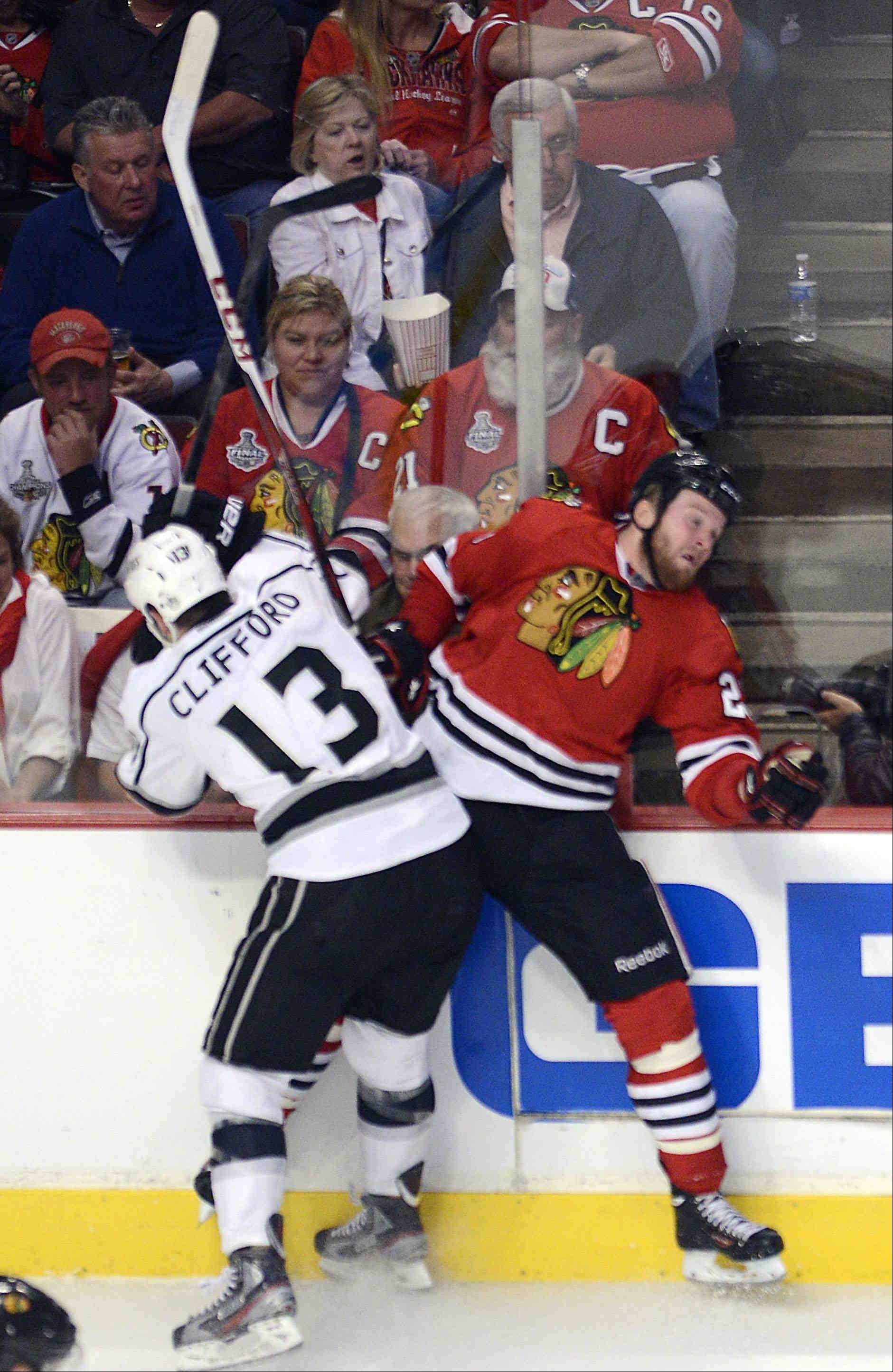Los Angeles Kings left wing Kyle Clifford checks Chicago Blackhawks left wing Bryan Bickell into the boards in the second period Saturday during the NHL Western Conference Finals Game 5 at the United Center in Chicago.