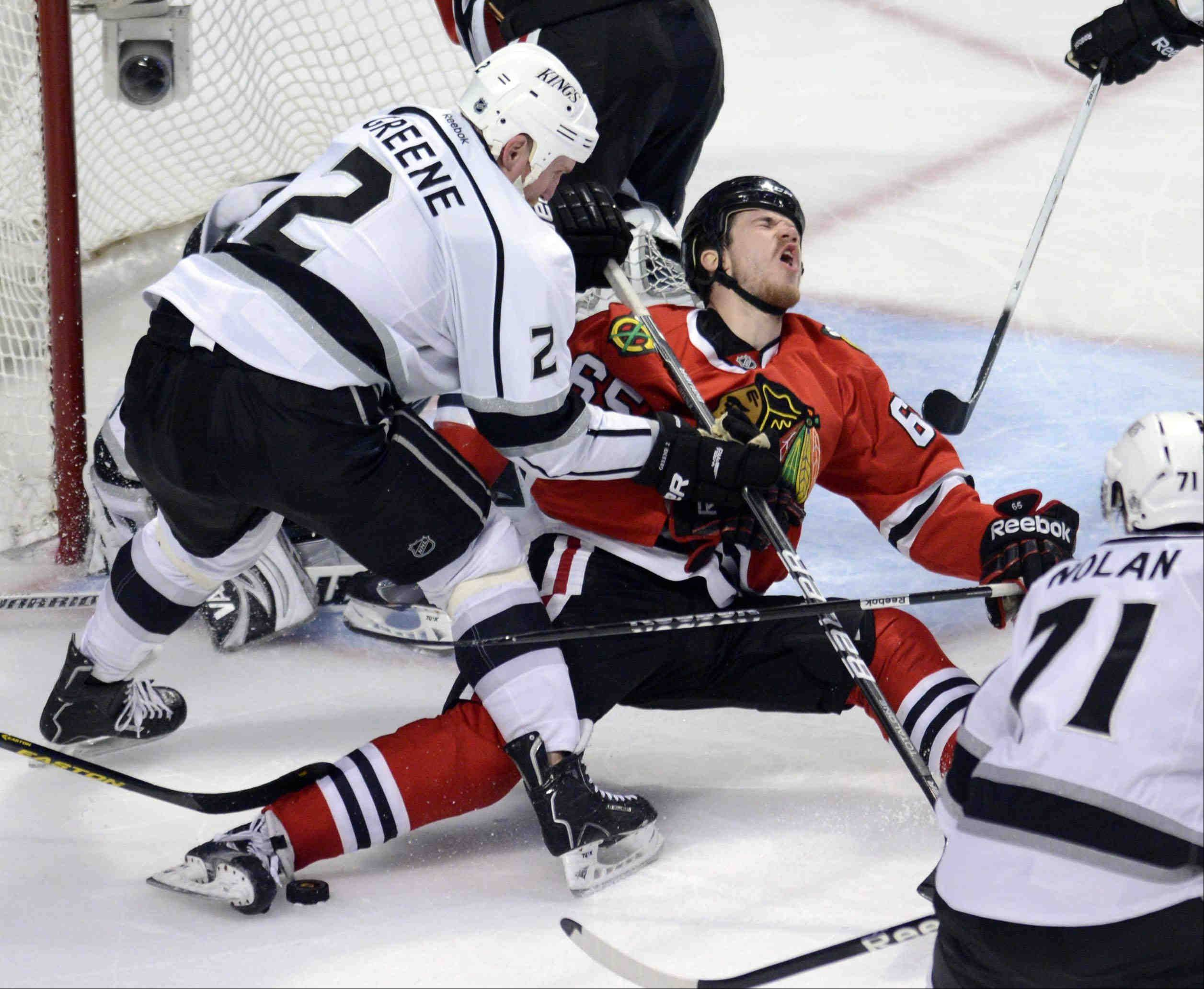 Los Angeles Kings defenseman Matt Greene cross checks Chicago Blackhawks center Andrew Shaw in front of the net Saturday during the NHL Western Conference Finals Game 5 at the United Center in Chicago.