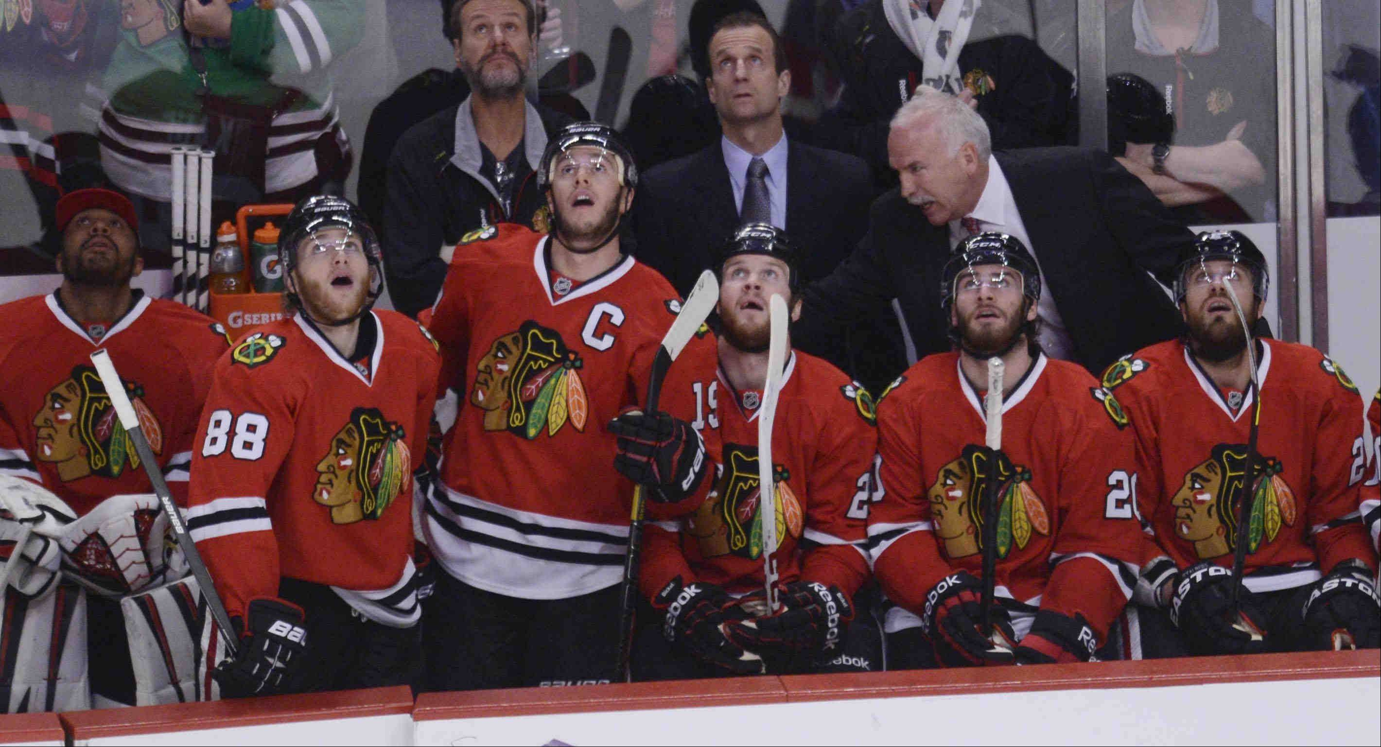 Chicago Blackhawks right wing Patrick Kane, left, and teammates watch the replay of his first-period goal against the Los Angeles Kings Saturday during the NHL Western Conference Finals Game 5 at the United Center in Chicago.