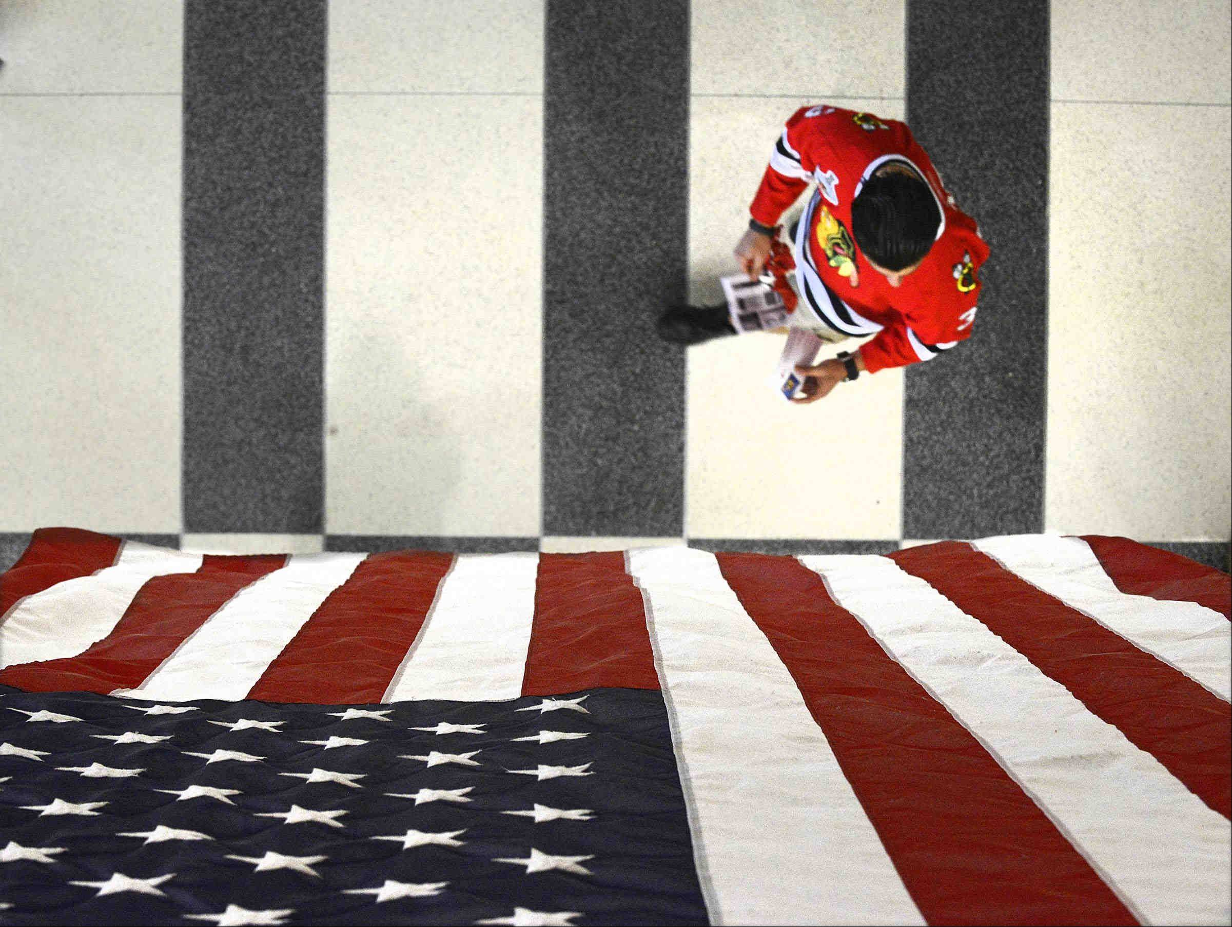 A Blackhawk fan walks under an American Flag on the concourse Saturday before the NHL Western Conference Finals Game 5 between the Chicago Blackhawks and the Los Angeles Kings at the United Center in Chicago.