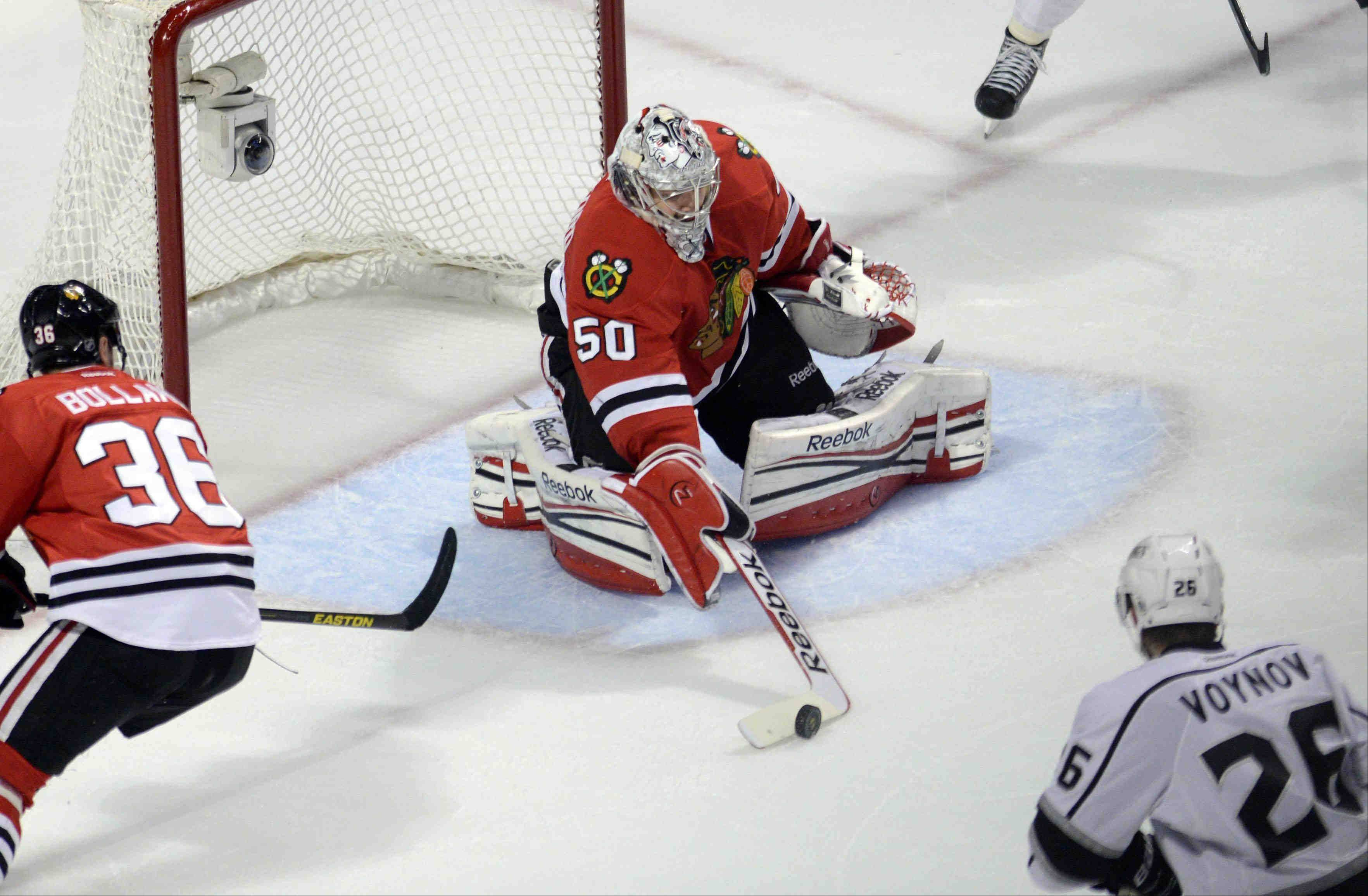 Chicago Blackhawks goalie Corey Crawford pokes the puck away form the net during an Los Angeles Kings power play Saturday during the NHL Western Conference Finals Game 5 at the United Center in Chicago.