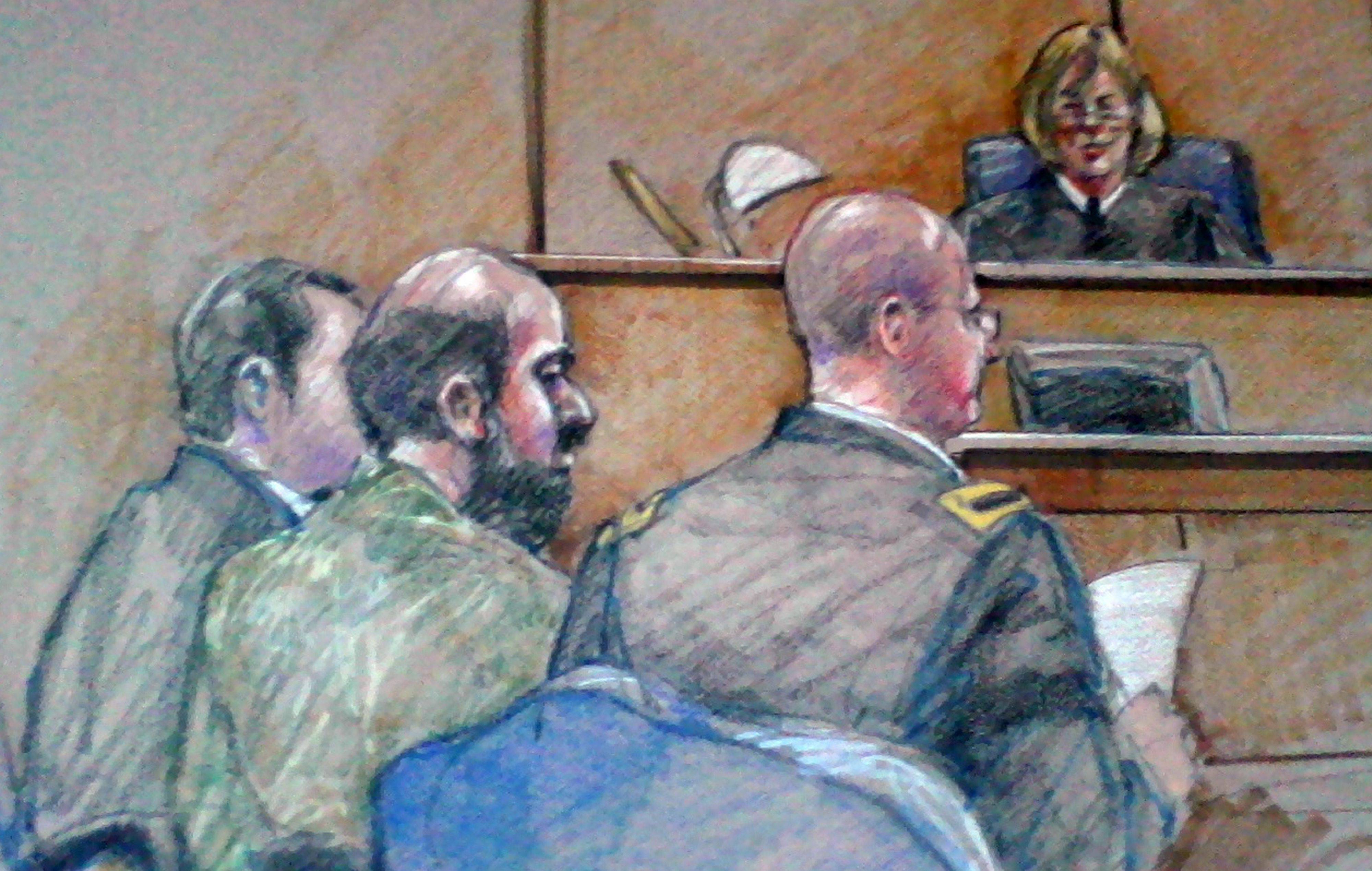 In this Dec. 18, 2012, courtroom sketch, U.S. Army Maj. Nidal Hasan, center foreground with back showing, is seen sitting between members of His defense team during a hearing in Fort Hood, Texas. The Army psychiatrist's trial was scheduled to begin last week.