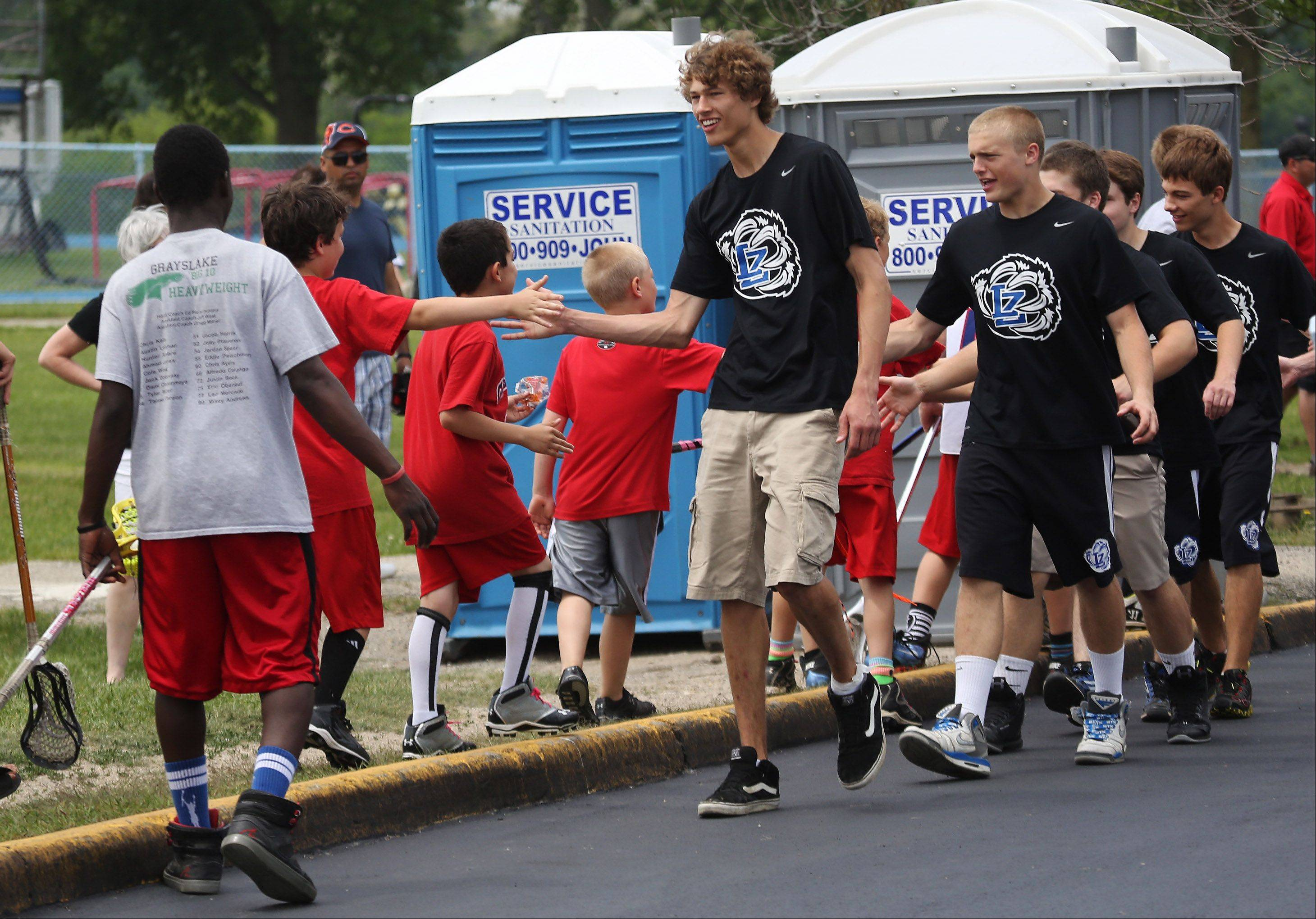 Parker Brown, left, and Travis Lores join other members of the Lake Zurich High School lacrosse team in shaking hands with kids along the parade route Sunday during a rally at the school after their team won the Lacrosse Cup state championship.