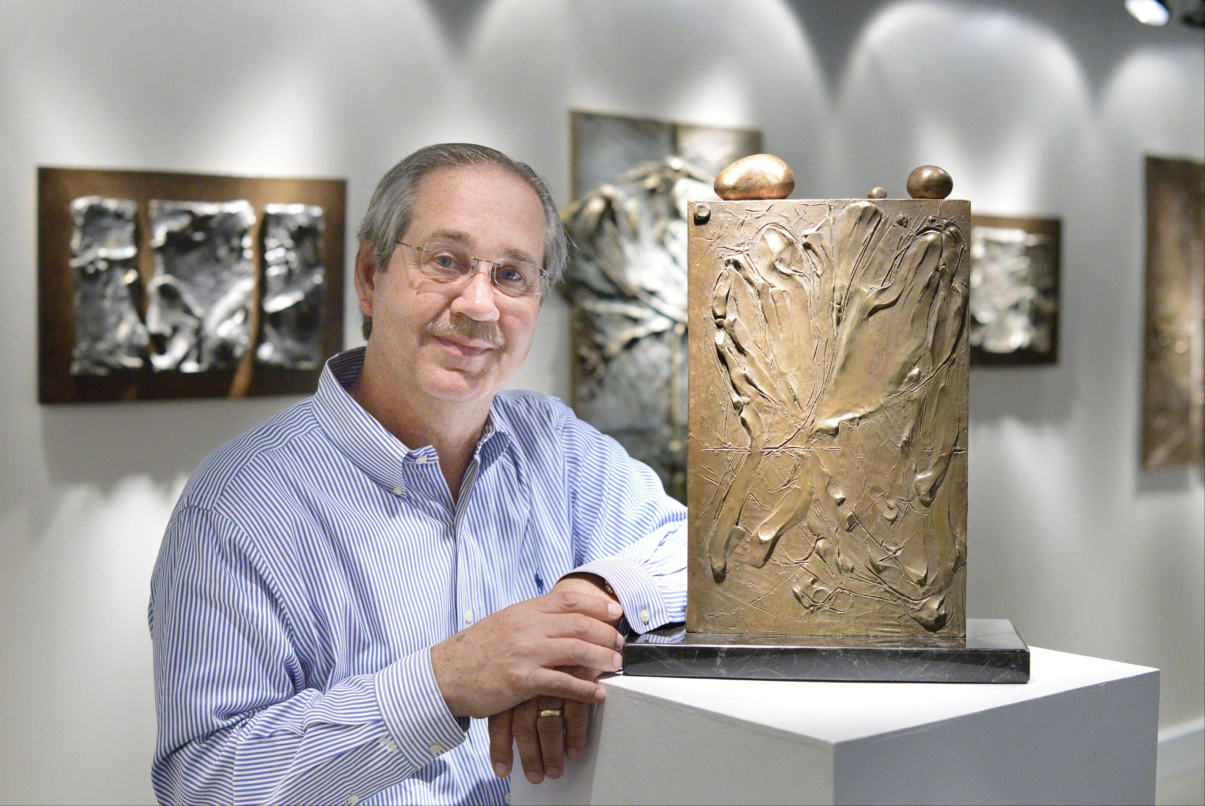"Artist Larry Johnson in his LK Johnson Studio and gallery in Geneva with bronze piece titled, ""Prayer Memorial for the Souls of Terezin."" Johnson retired from IBM and went back to what he studied in college — sculpting. His studio's grand opening will be July 19-20."