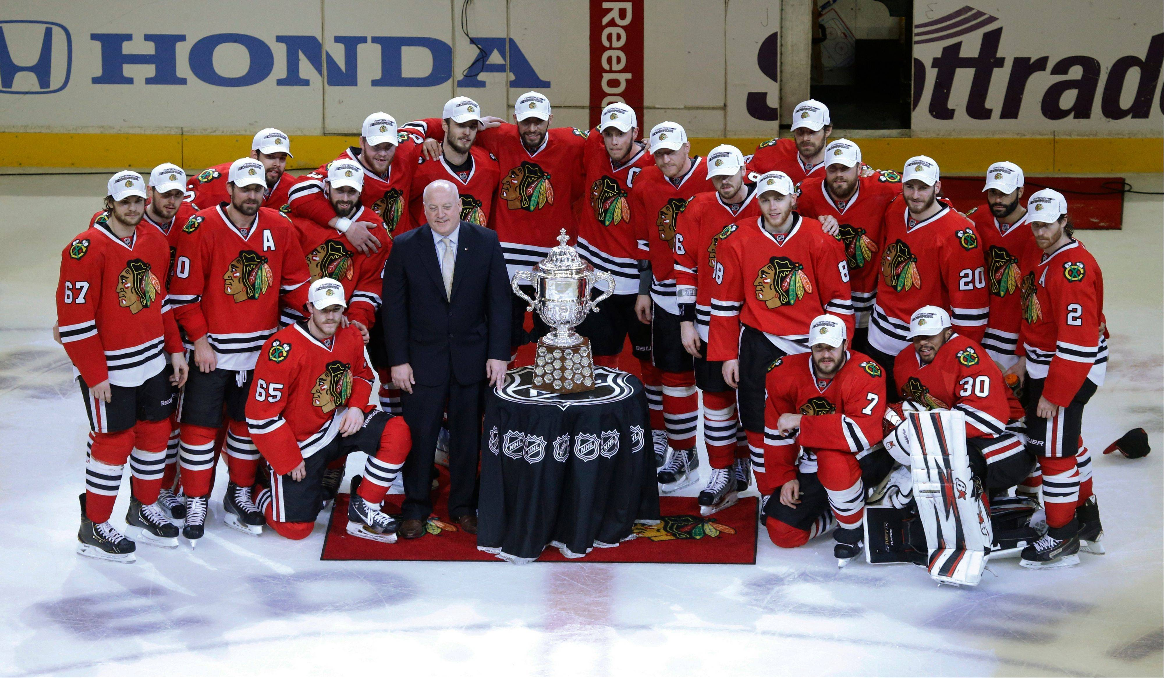 Chicago Blackhawks players pose with NHL deputy commissioner Bill Daly and the Western Conference Championship trophy as they win over Los Angeles Kings 4-3 in the second overtime period in Game 5 of the NHL hockey Stanley Cup playoffs Western Conference finals, Saturday, June 8, 2013, in Chicago. The Blackhawks advance to the Stanley Cup finals.