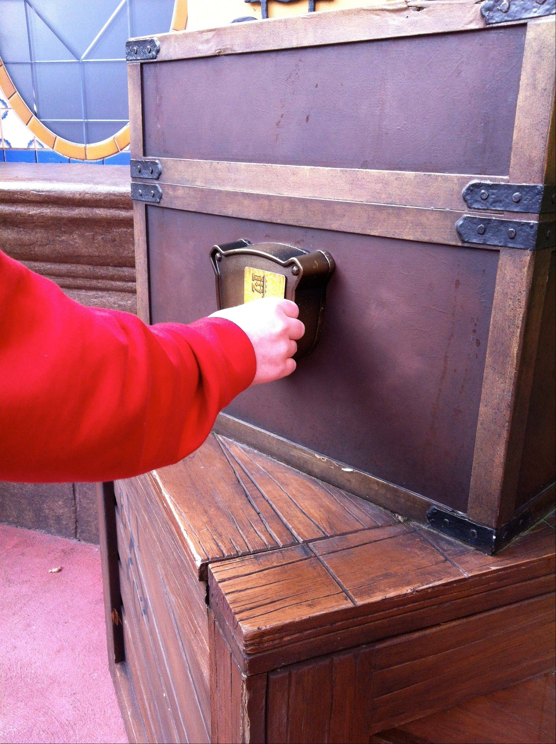 "A Walt Disney World guest swipes his key card while playing the ""Sorcerers of the Magic Kingdom"" game at the Magic Kingdom theme park."