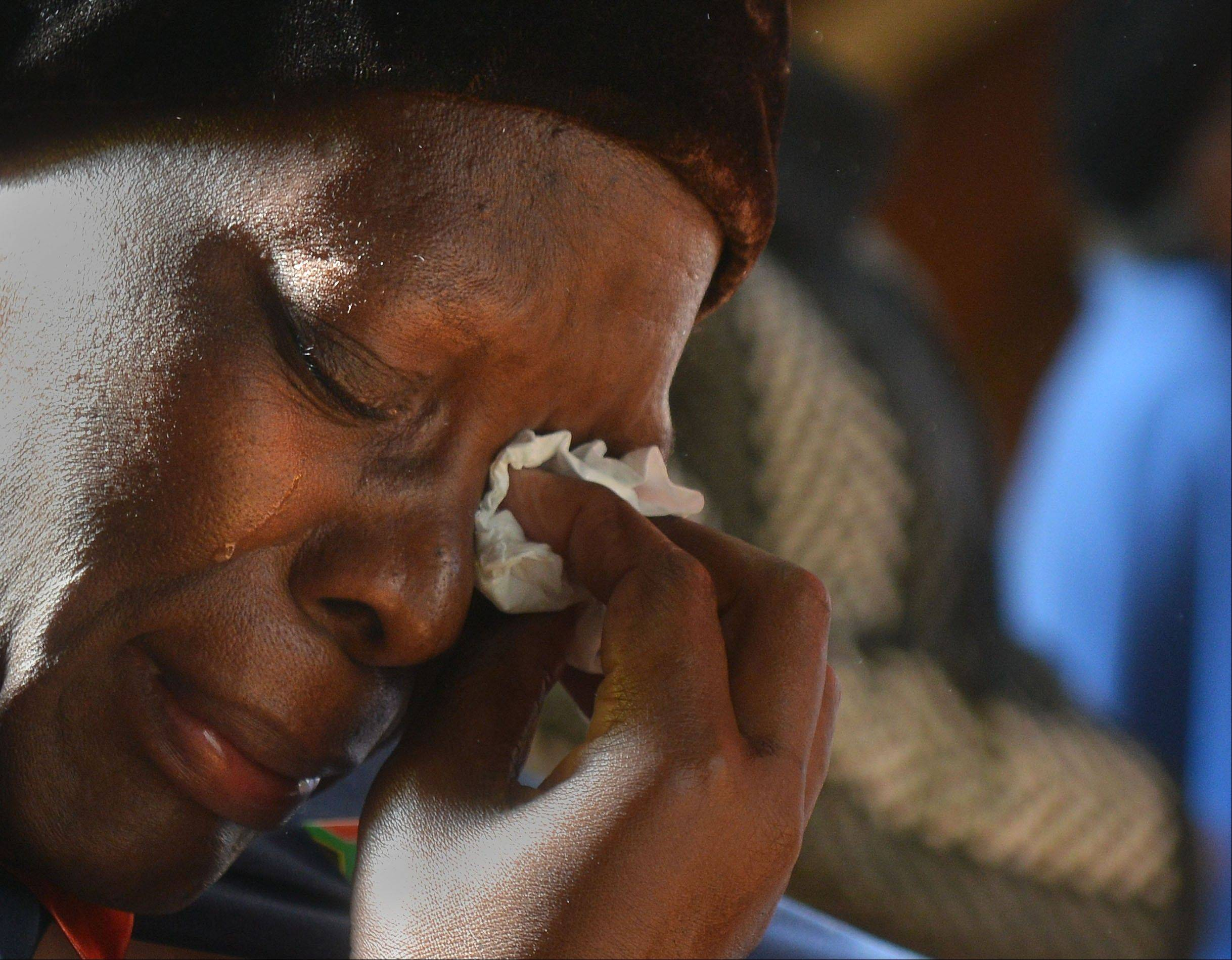 A worshipper weeps as she attends Mass at a Catholic church in Soweto, South Africa, Sunday. Churchgoers were urged to pray for former President Nelson Mandela, who has been hospitalized with a lung infection.