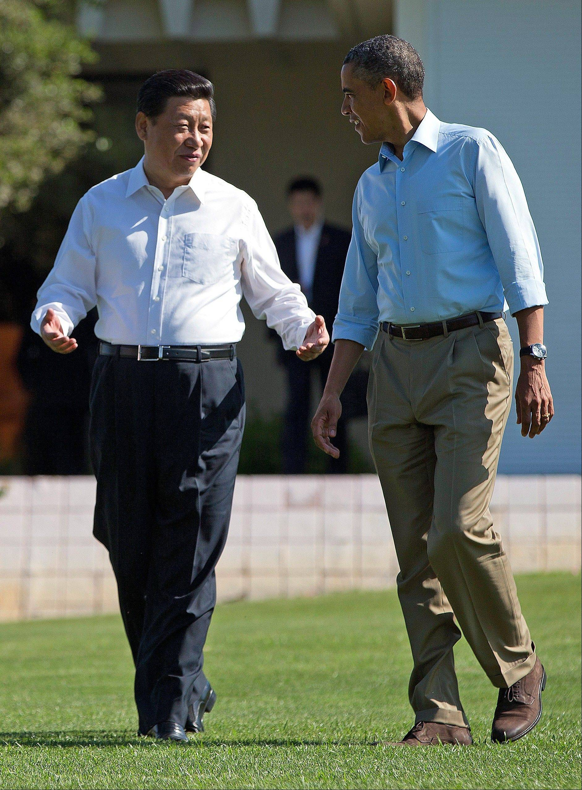 "President Barack Obama and Chinese President Xi Jinping walk at the Annenberg Retreat of the Sunnylands estate Saturday in Rancho Mirage, Calif. Obama told reporters his meetings with Xi have been ""terrific,"" while saying it is critical the U.S. and China reach a ""firm understanding"" on cyber issues."