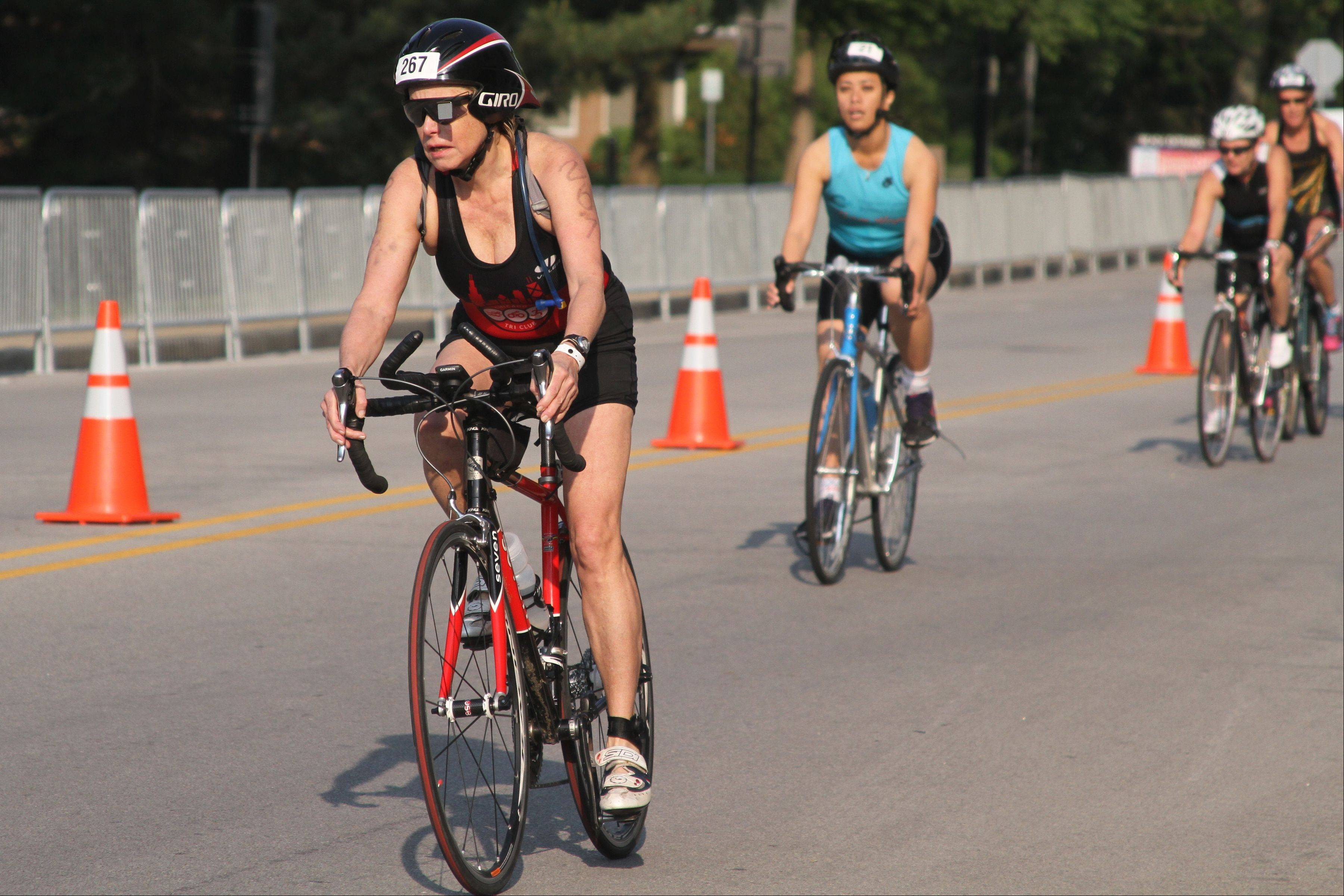 Athletes bike down Jackson Street in downtown Naperville as a part of the second leg of the Athleta Esprit de She Triathlon through downtown Naperville on Sunday. The triathlon started at Centennial Beach with a half-mile swim, followed by a 14.2-mile bike ride and a 3.1-mile run.