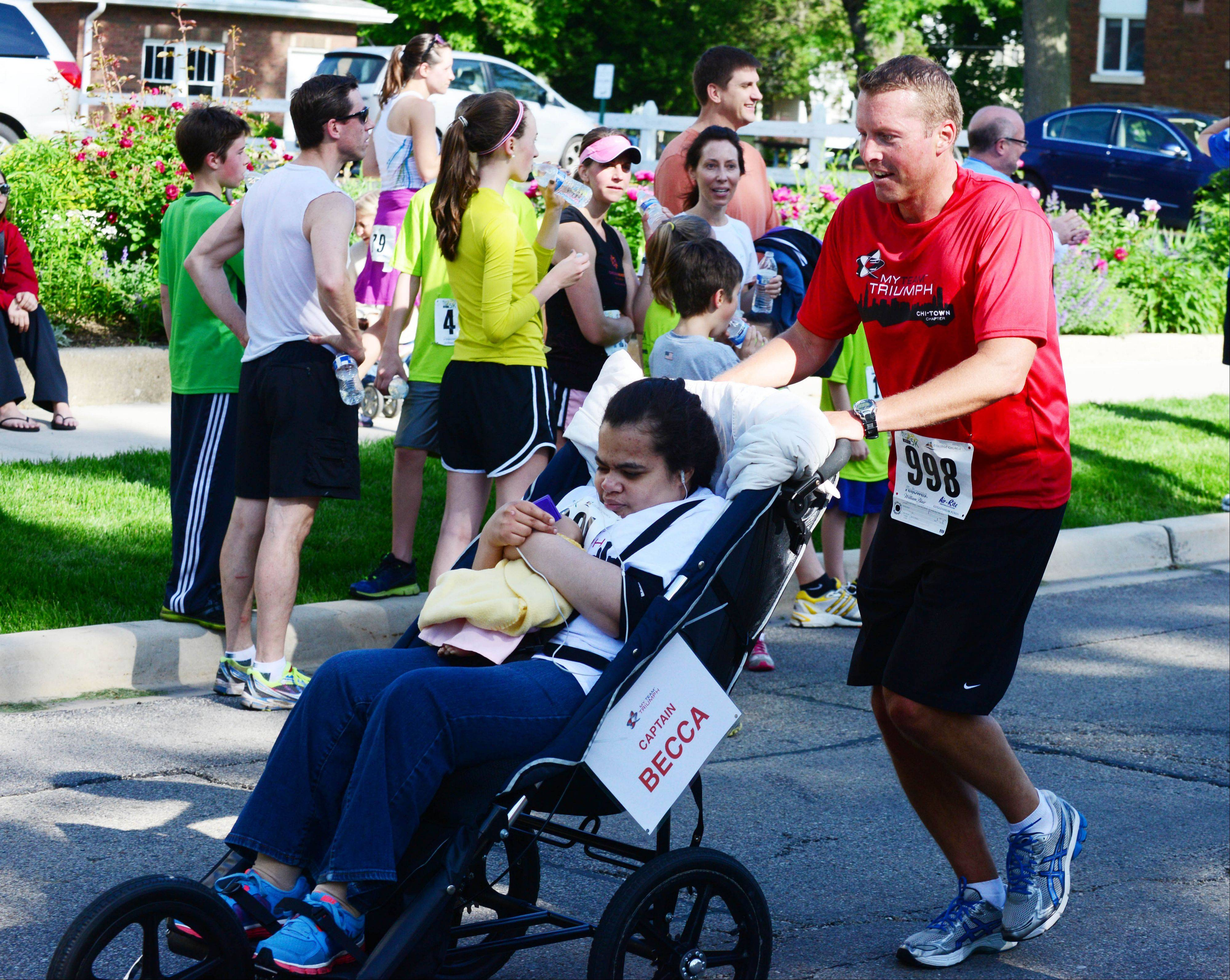 MyTeam Triumph President Brian Merkle of Naperville pushes Becca Tally across the finish line at Wheaton's Run For The Stars 5K race Saturday. A group of 21 runners helped seven people with disabilities compete in the race.