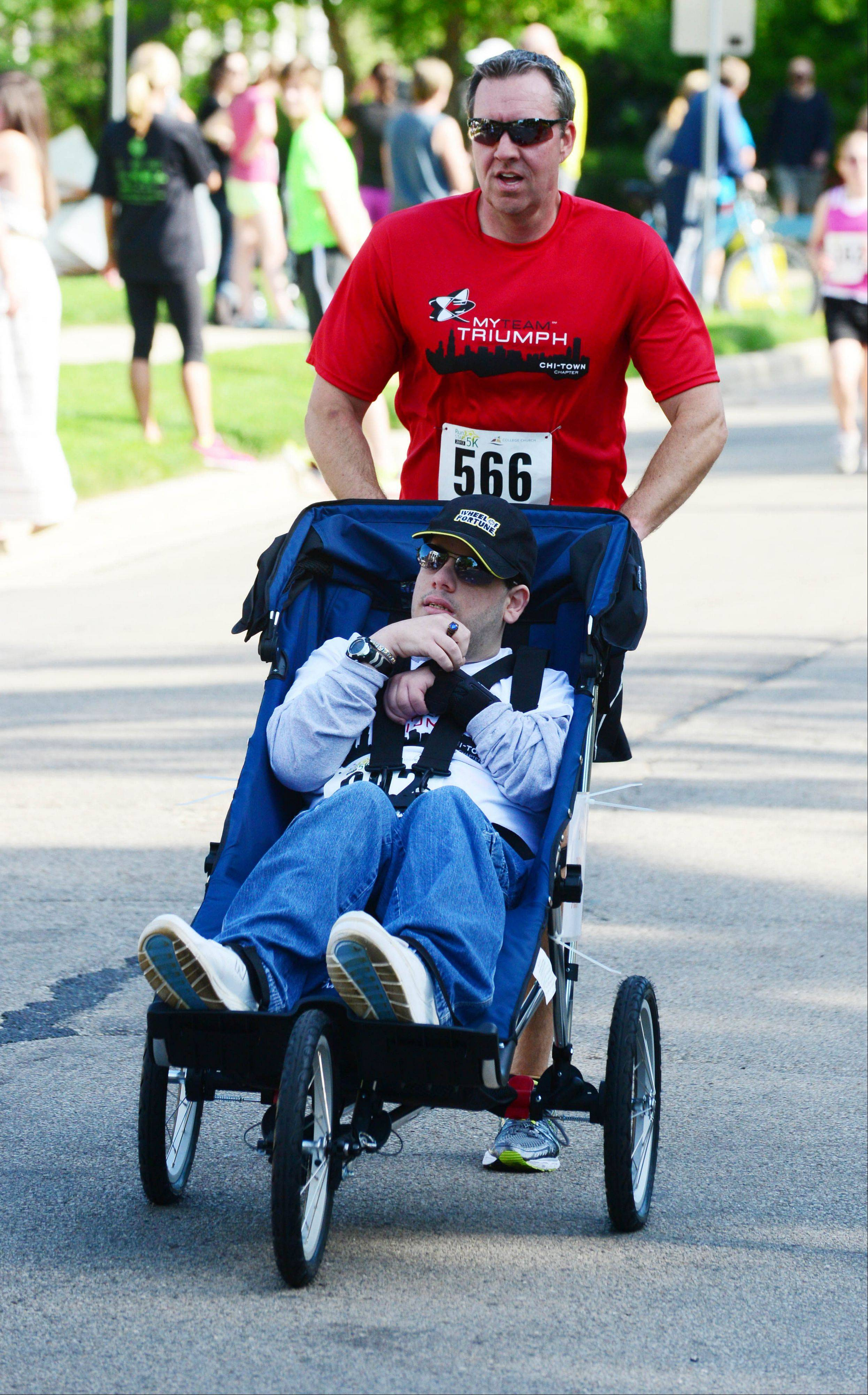 "Calling his race experience ""awesome,"" 21-year-old Alex Brescia of Hoffman Estates nears the finish line with help from myTeam Triumph ""angel"" runner Trevor O'Malley of Naperville."