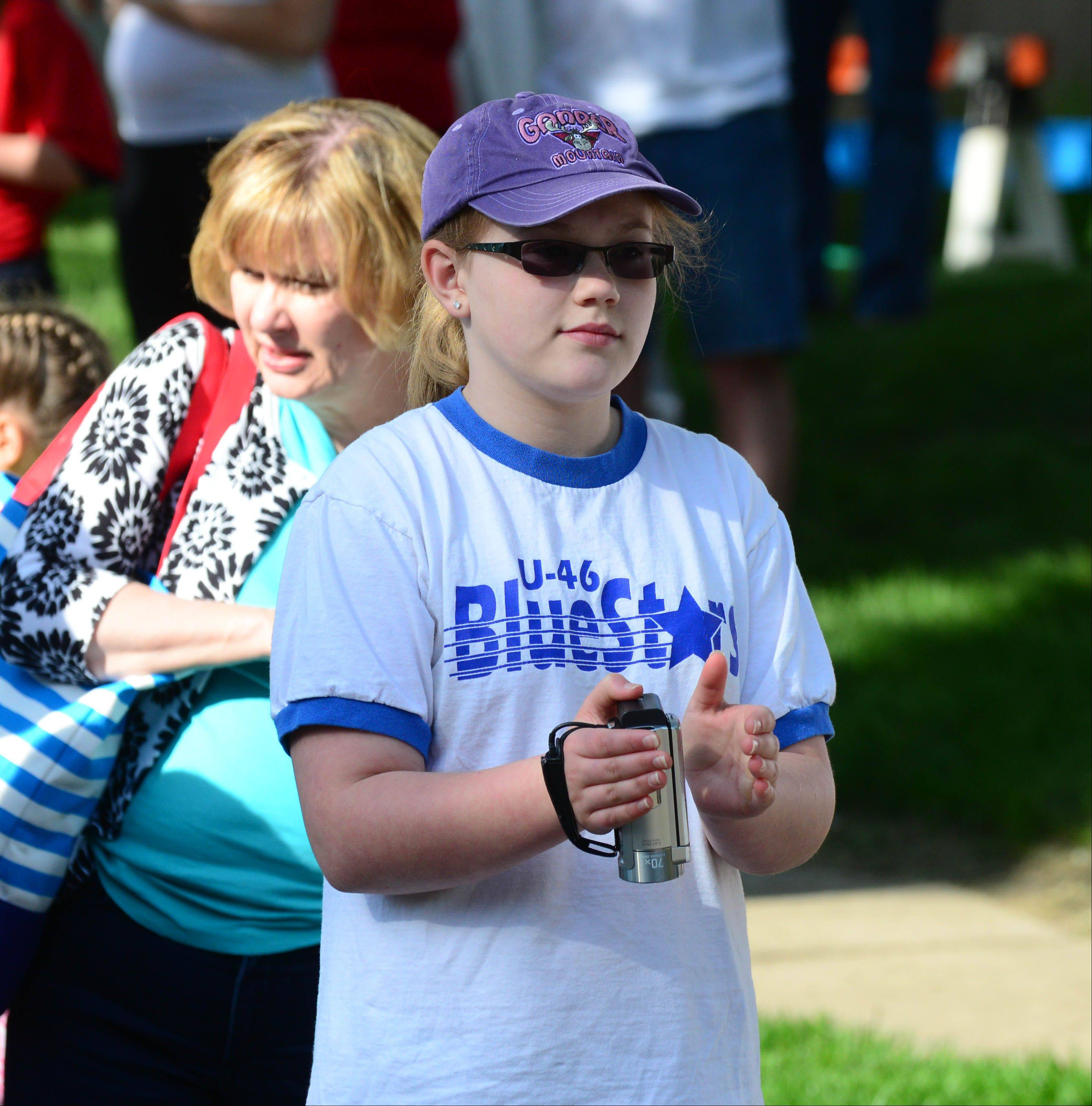 Rooting for the myTeam Triumph trio pushing her 9-year-old brother Jeremy in a wheelchair stroller, Cara Johnson, 13, of Streamwood cheers on the runners Saturday in Wheaton's Run For The Stars 5-K.