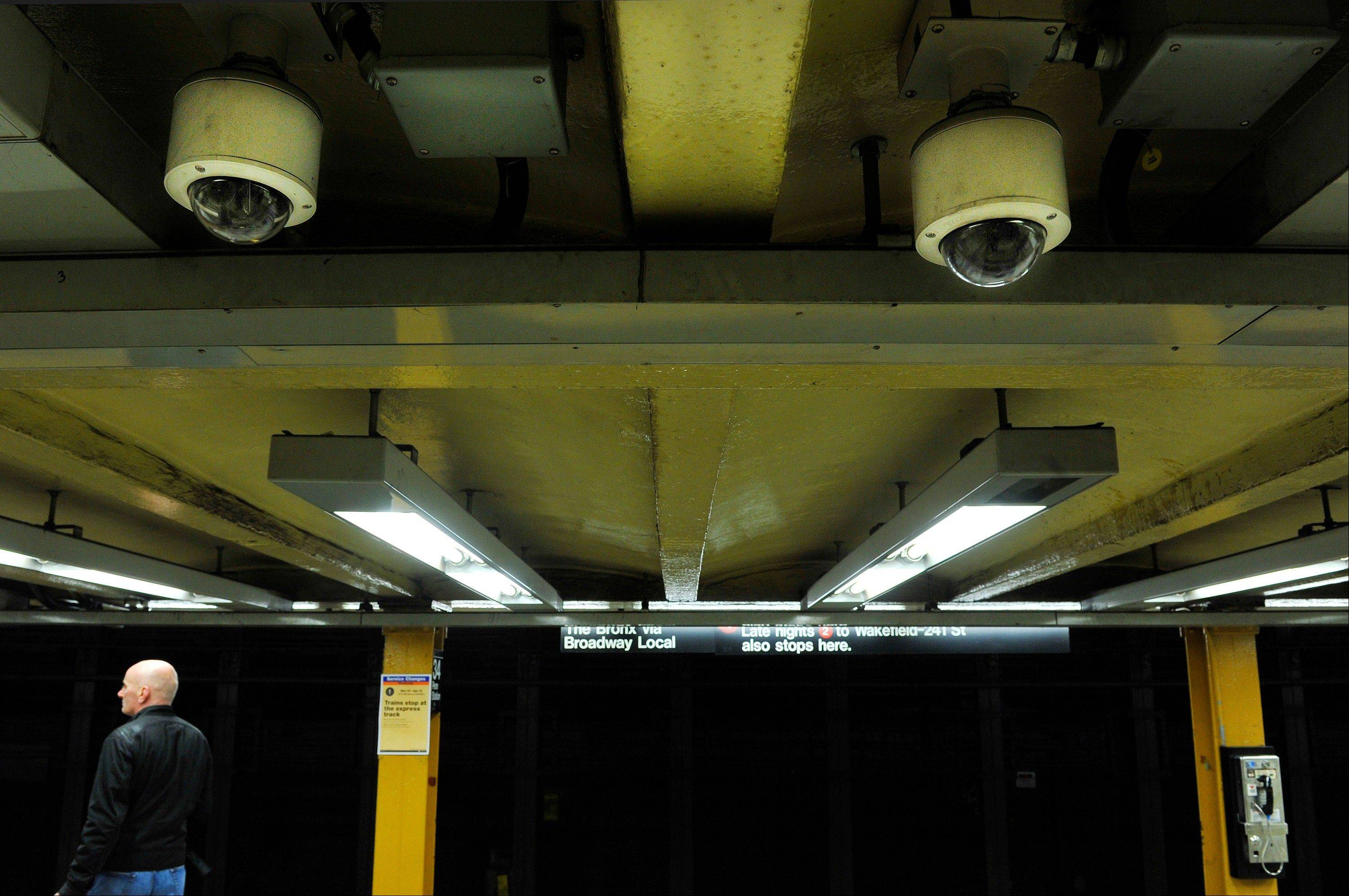 Two ceiling-mounted video surveillance cameras watch as a man awaits the arrival of a No. 1 subway train at the 34th Street station, in New York.
