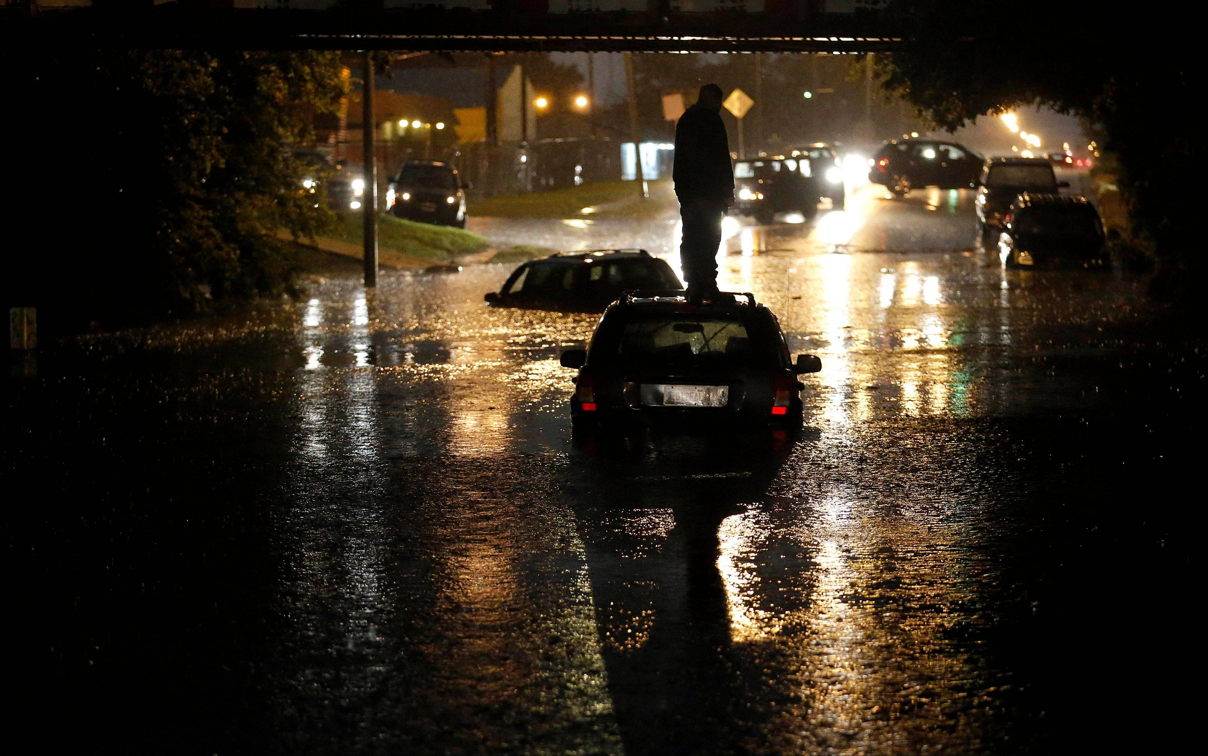 A man stands on top of his car as it is flooded in Oklahoma City.