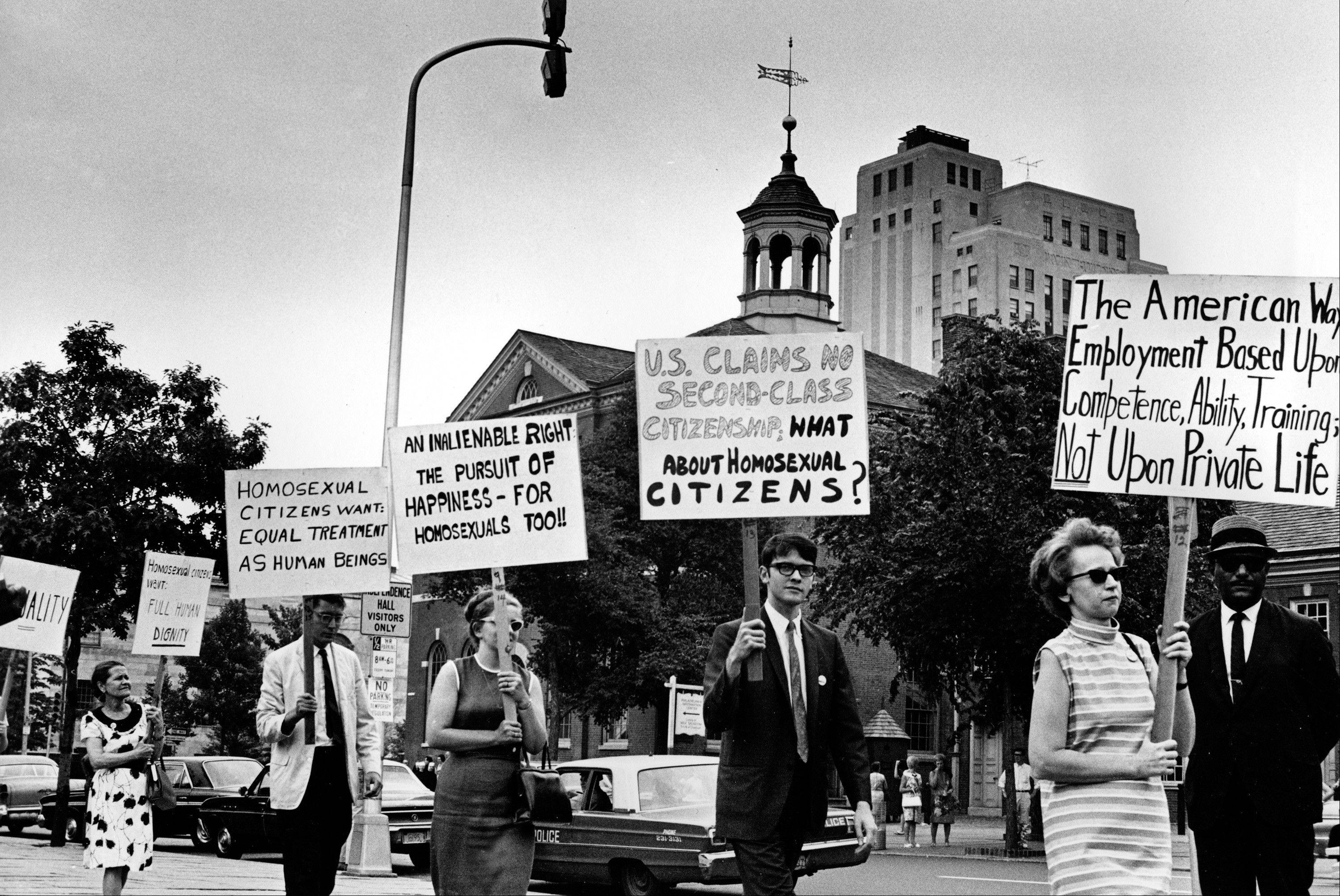Kay Tobin Lahusen, right, and other demonstrators carry signs calling for protection of homosexuals from discrimination as they march in a picket line in front of Independence Hall in Philadelphia.