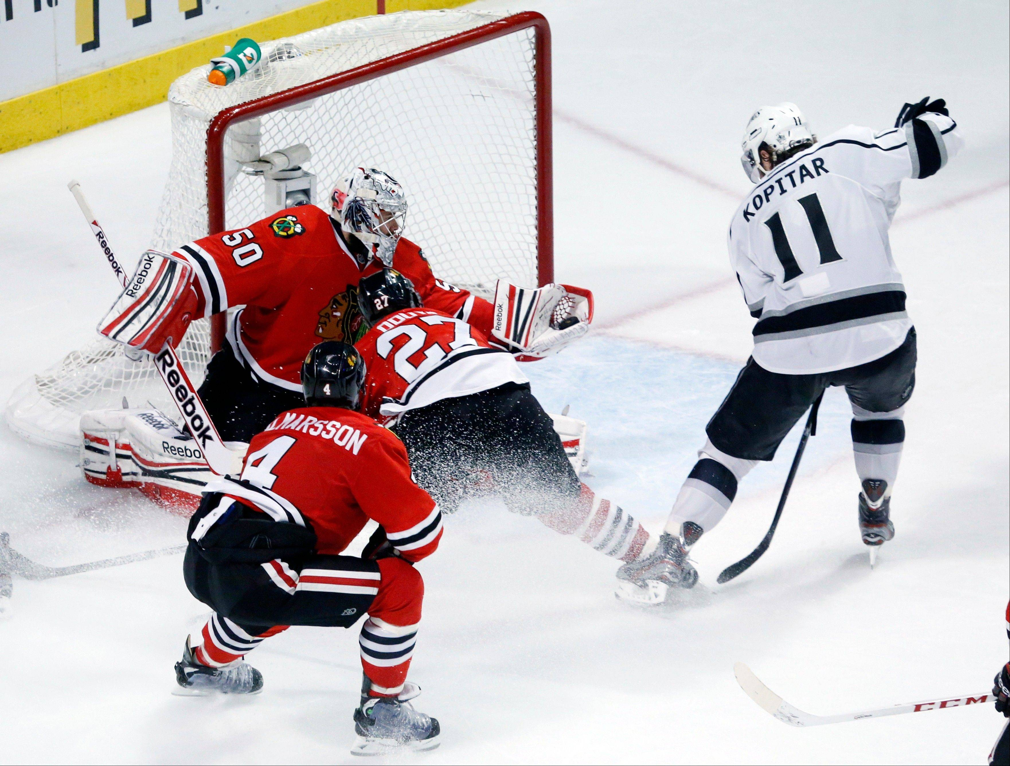 Chicago Blackhawks goalie Corey Crawford (50) grabs the puck in front of Los Angeles Kings center Anze Kopitar (11) during the first overtime period in Game 5 of the NHL hockey Stanley Cup playoffs Western Conference finals Saturday, June 8, 2013, in Chicago.