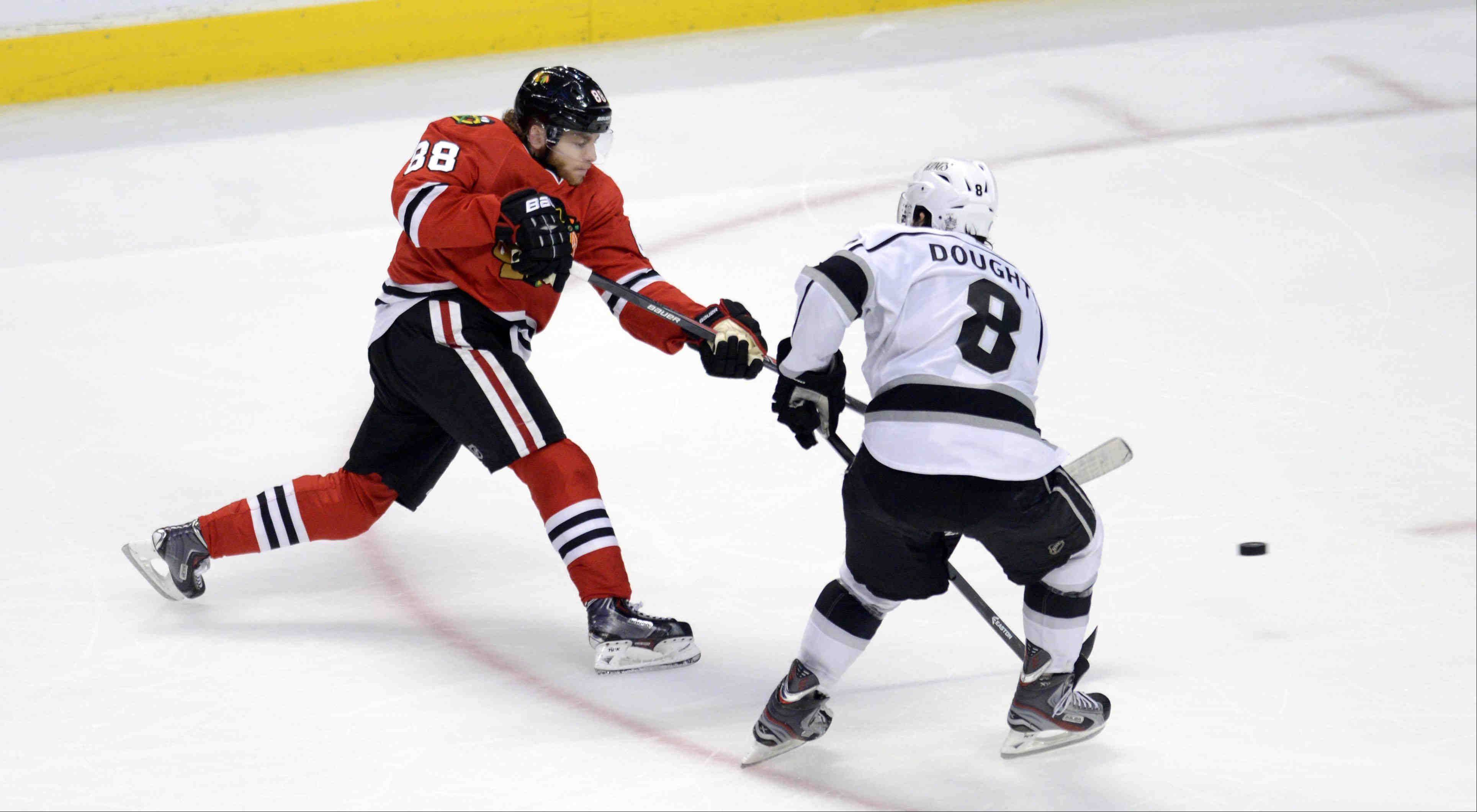 Blackhawks right wing Patrick Kane shoots in the second period against the defense of Los Angeles Kings defenseman Drew Doughty Saturday during the NHL Western Conference Finals Game 5 at the United Center in Chicago.