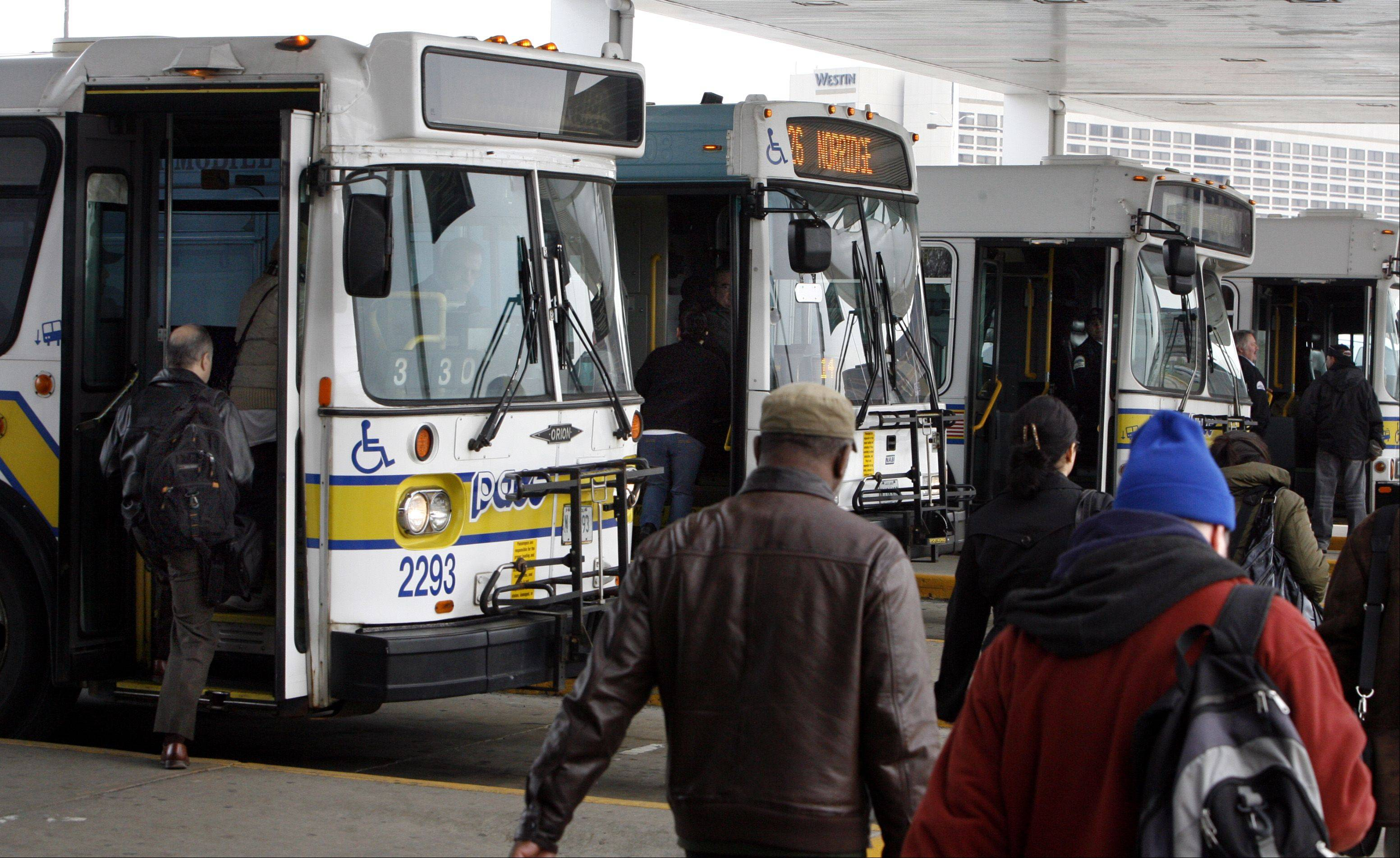 Riders head toward Pace buses lined up during the morning rush hour at the CTA Blue Line station on River Road in Rosemont.