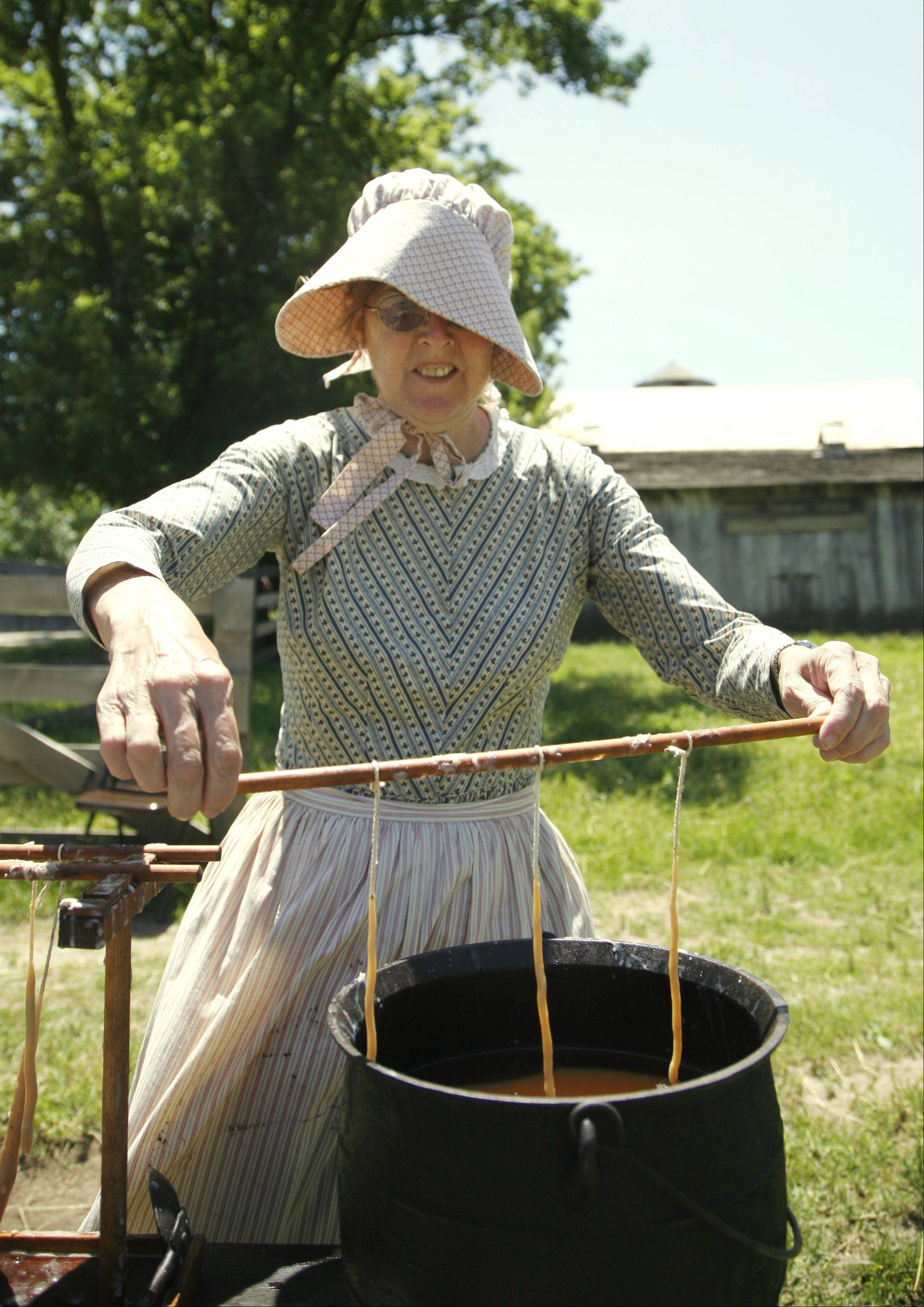 Helen Bauer of Campton Hills demonstrates candle making during a previous 1840s Day at Garfield Farm Museum in La Fox. This year�s event is set for noon to 4 p.m. Sunday, June 16.