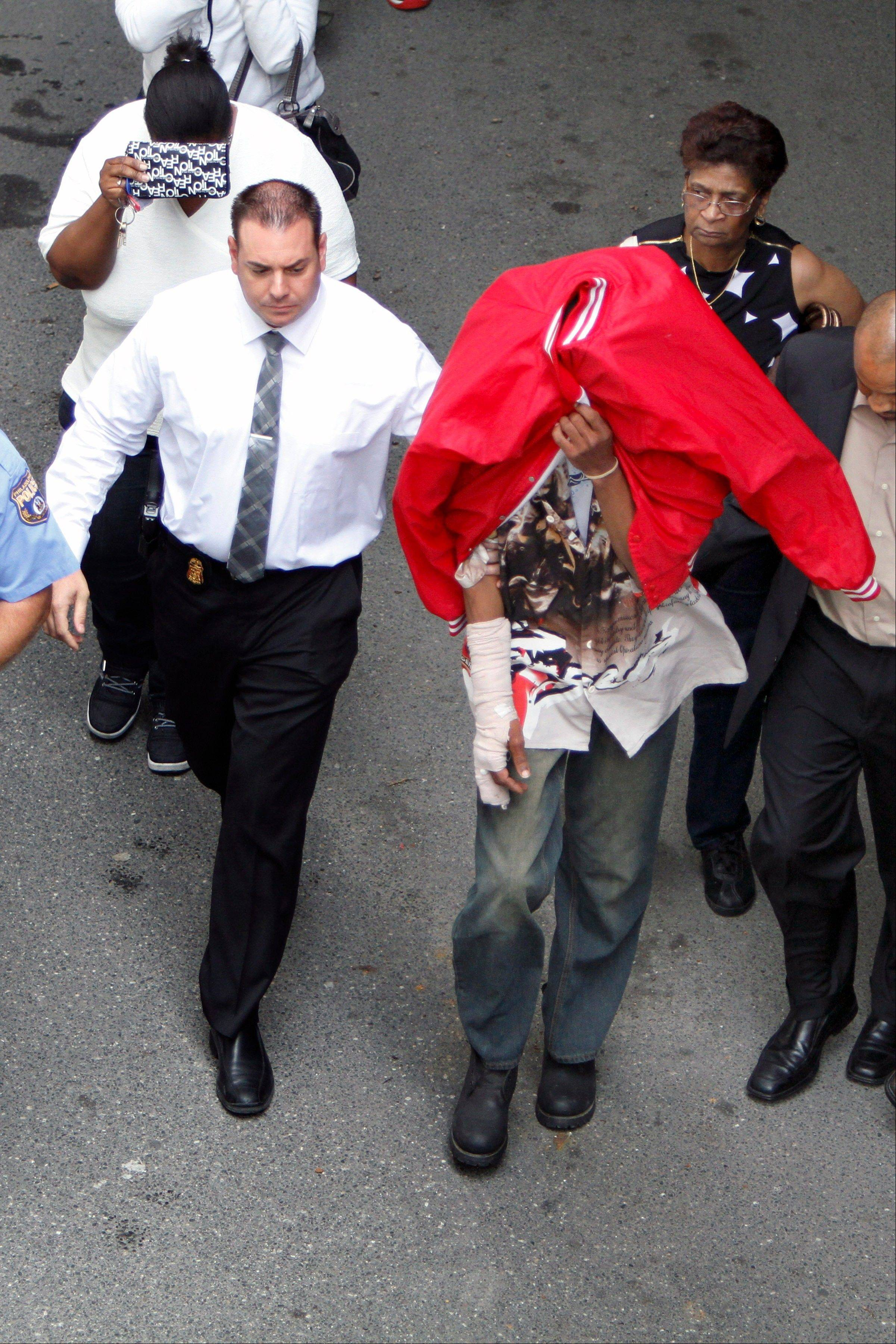 Sean Benschop, center, with red jacket over his head, walks with investigators as he arrives at the Philadelphia Police Department�s Central Detectives Division Saturday in Center City Philadelphia. Benschop, the heavy equipment operator accused of being high on marijuana when a downtown building collapsed onto a thrift store, killing six people, turned himself in on Saturday to face charges in the deaths, police said.
