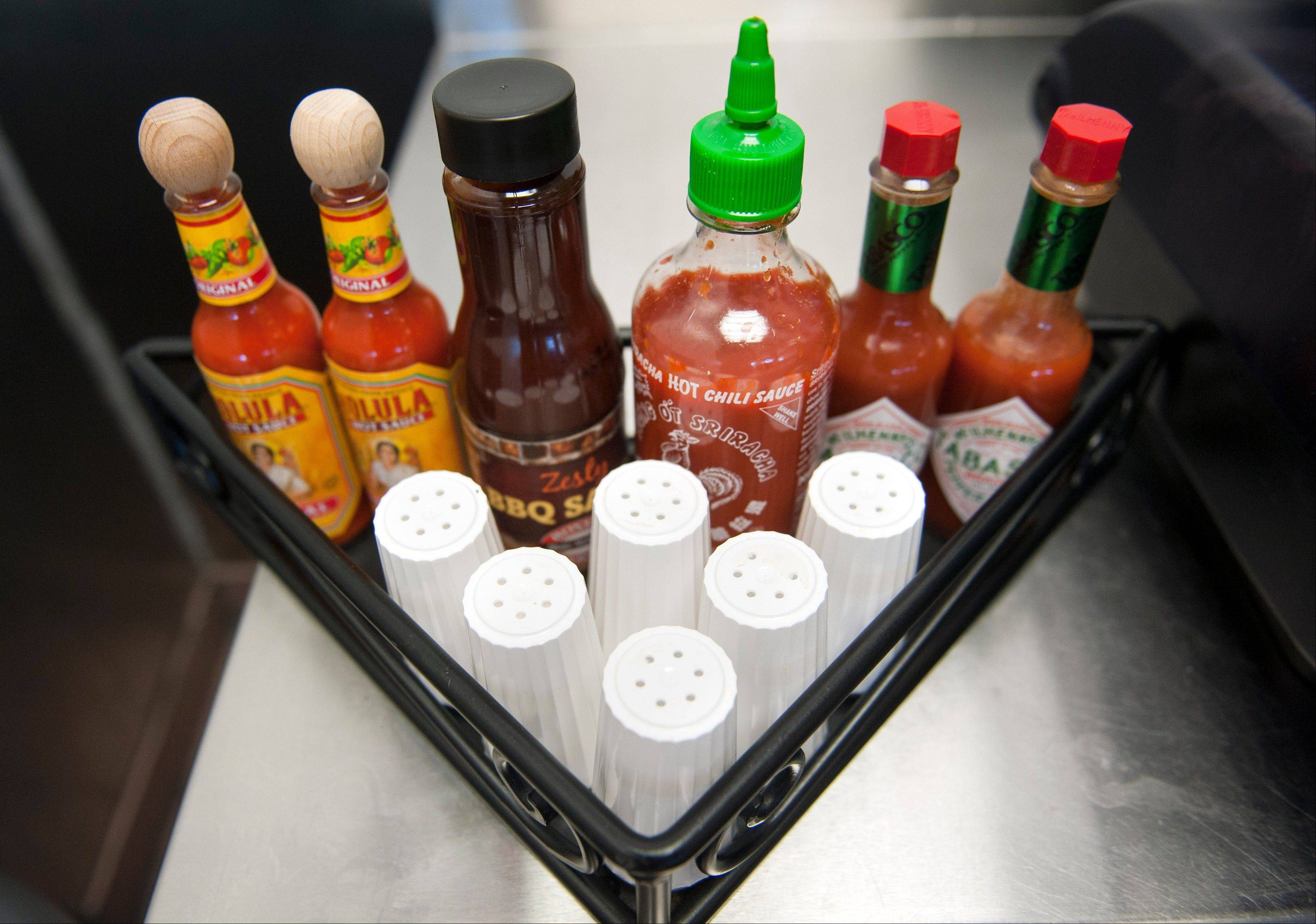 Salt shakers and other condiments sit on a beverage dispenser table at a Boston Market restaurant in Alexandria, Va. Boston Market has removed the salt shakers from the tables in their restaurants nationwide placing them with other condiments on the beverage dispenser table.