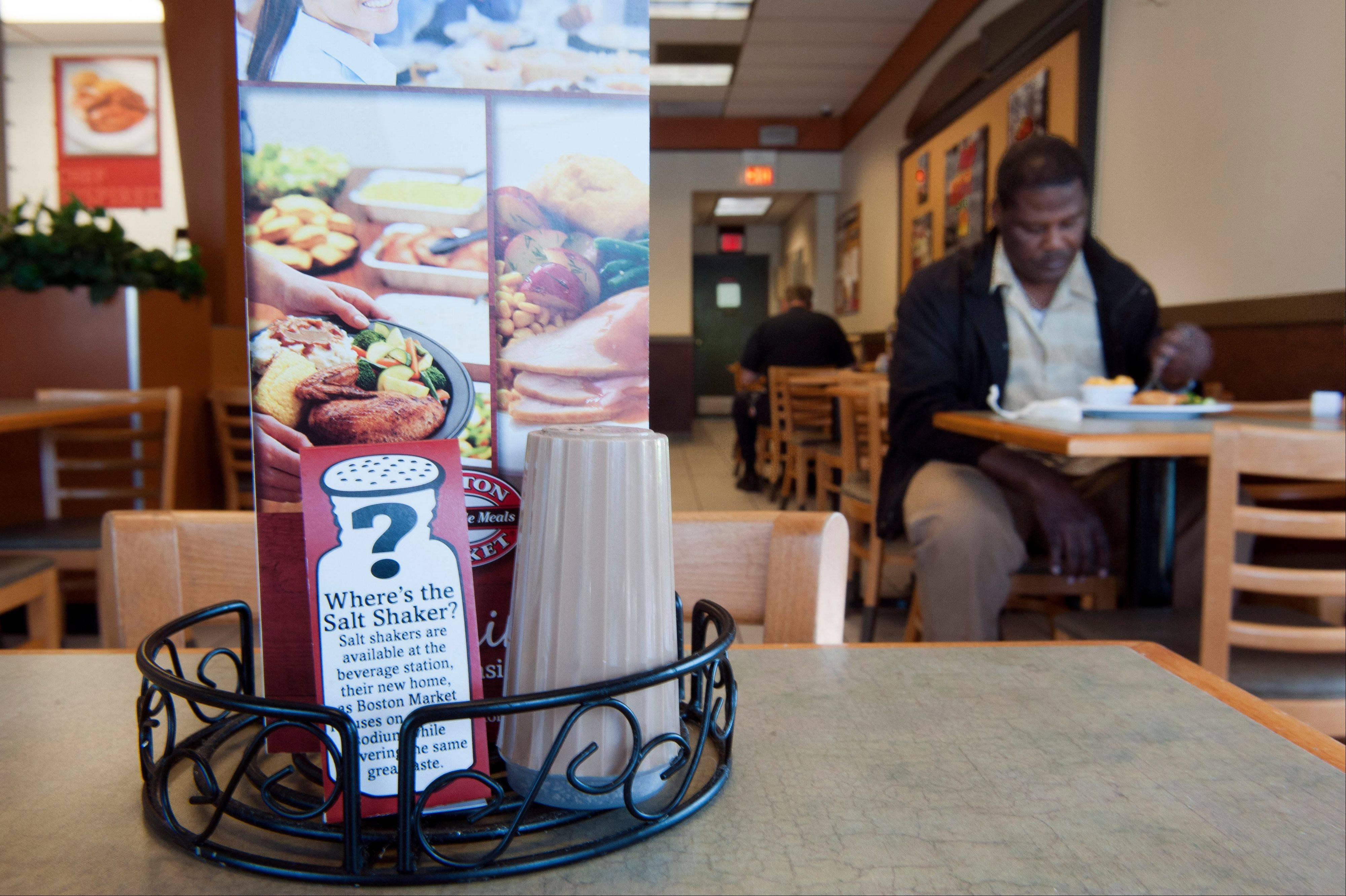 An advisory on salt shakers sits on a table at a Boston Market restaurant in Alexandria, Va. A surprising new report questions how sharply Americans should cut back on salt.