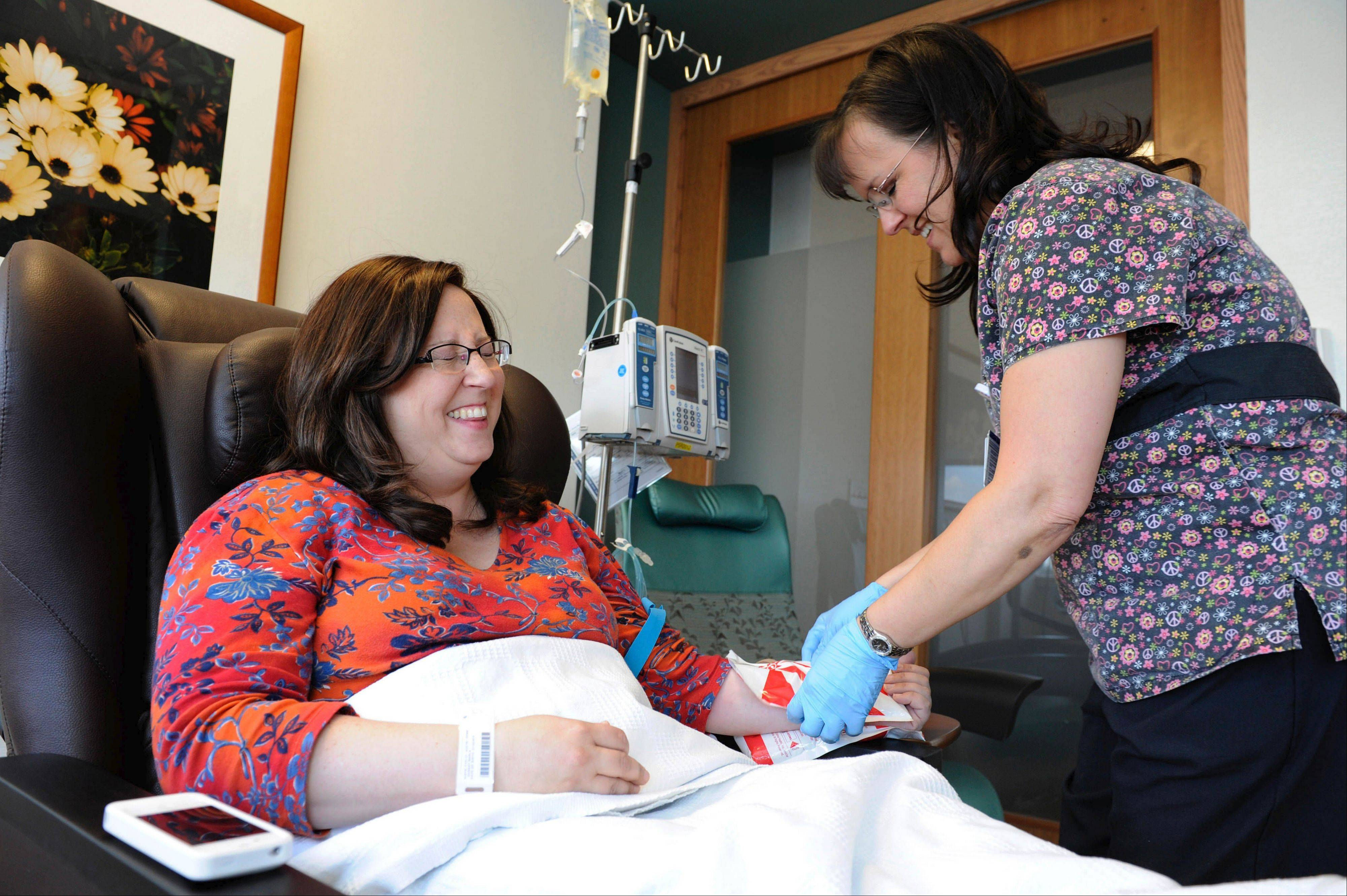 Marla Dansky, left, shares a light moment with registered nurse Joy Overton before receiving chemotherapy at the Duke University Cancer Center.