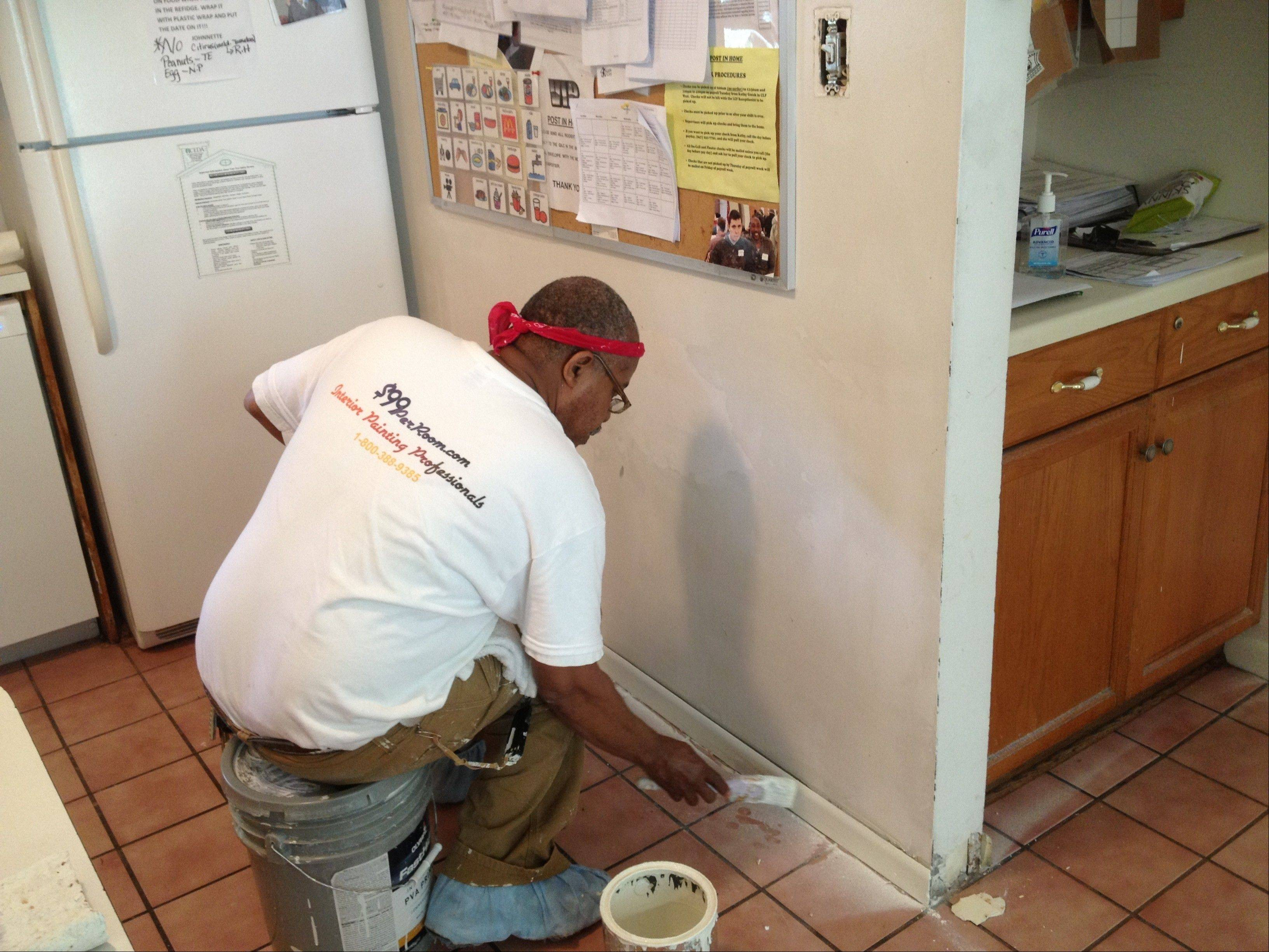 Jerome Christian, an employee of $99PerRoom, paints a kitchen wall at one of two Little City group homes in Schaumburg that he and other volunteers helped renovate Monday. The effort was part of the real estate firm Koenig & Strey's first Kindness Week.