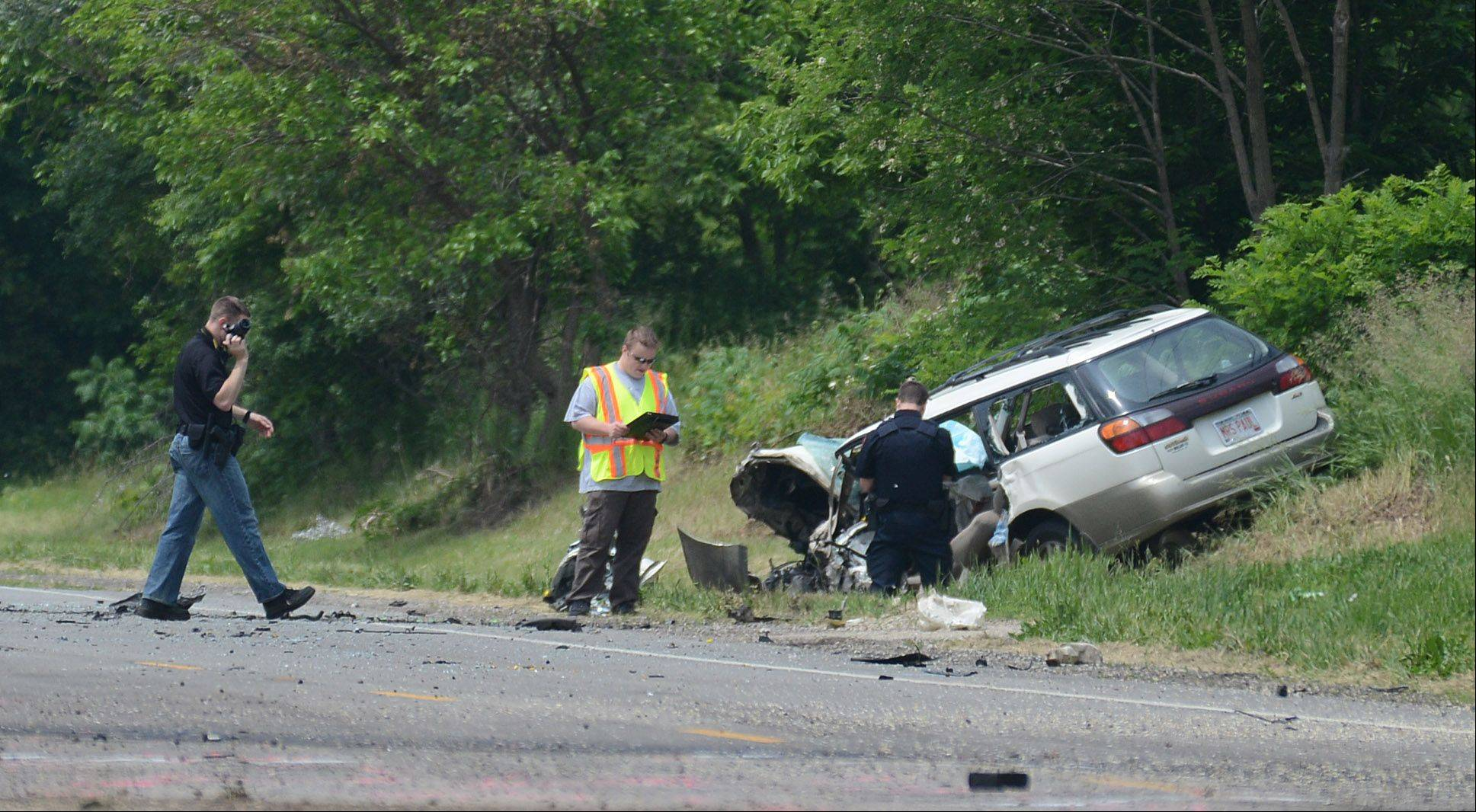 Officials check over the car that was involved in a fatal crash Monday on Route 173, in an unincorporated area near Fox Lake.