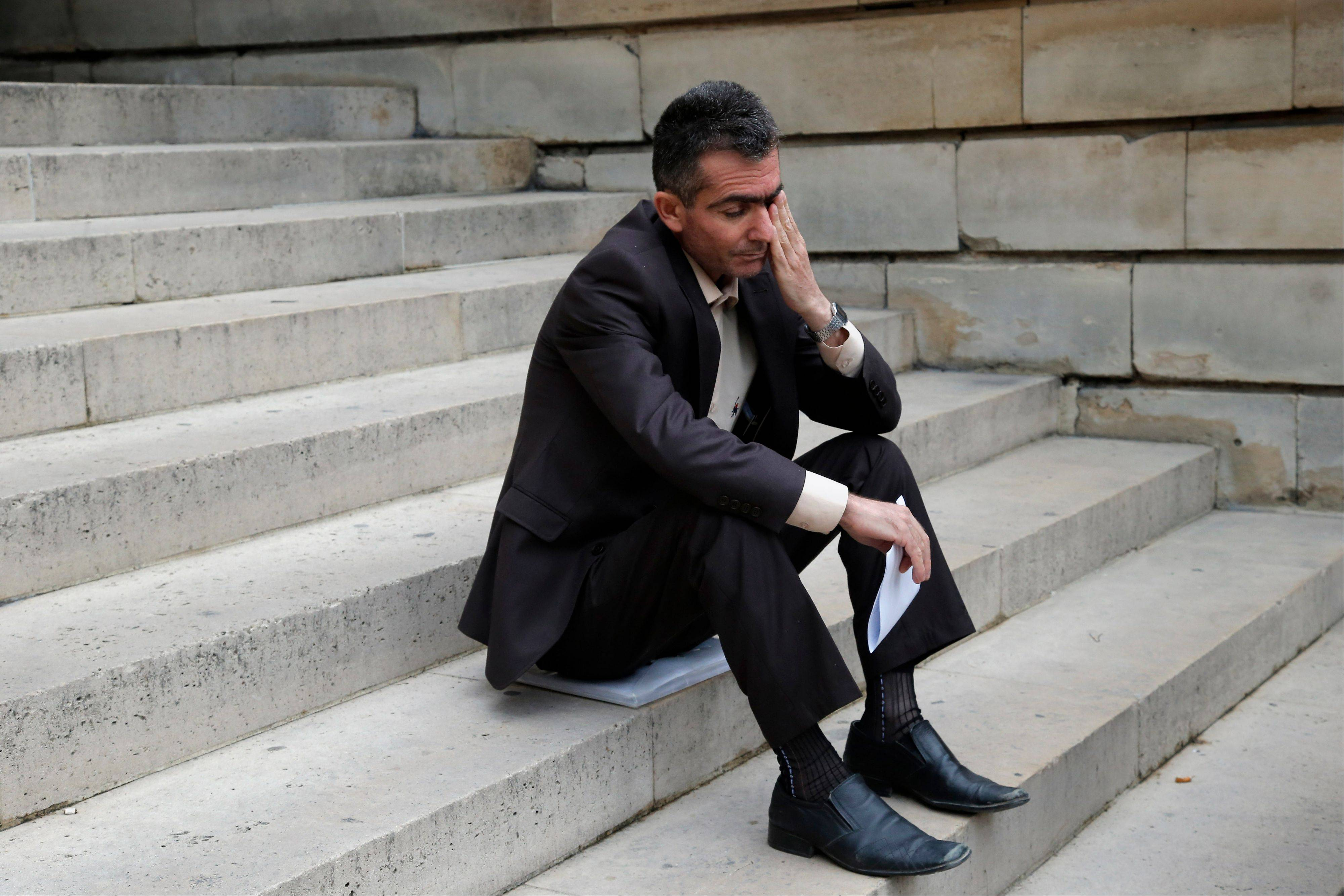 Kamil Abdulqadir Wais Mohammed sits on the steps of Paris court as he arrives at court to file a legal complaint Monday. Twenty victims of Saddam Hussein's 1988 chemical weapons attack on the Kurdish town of Halabja are demanding a French judicial investigation into companies that supplied the materials. Halabja marked the deadliest chemical weapons attack against civilians.