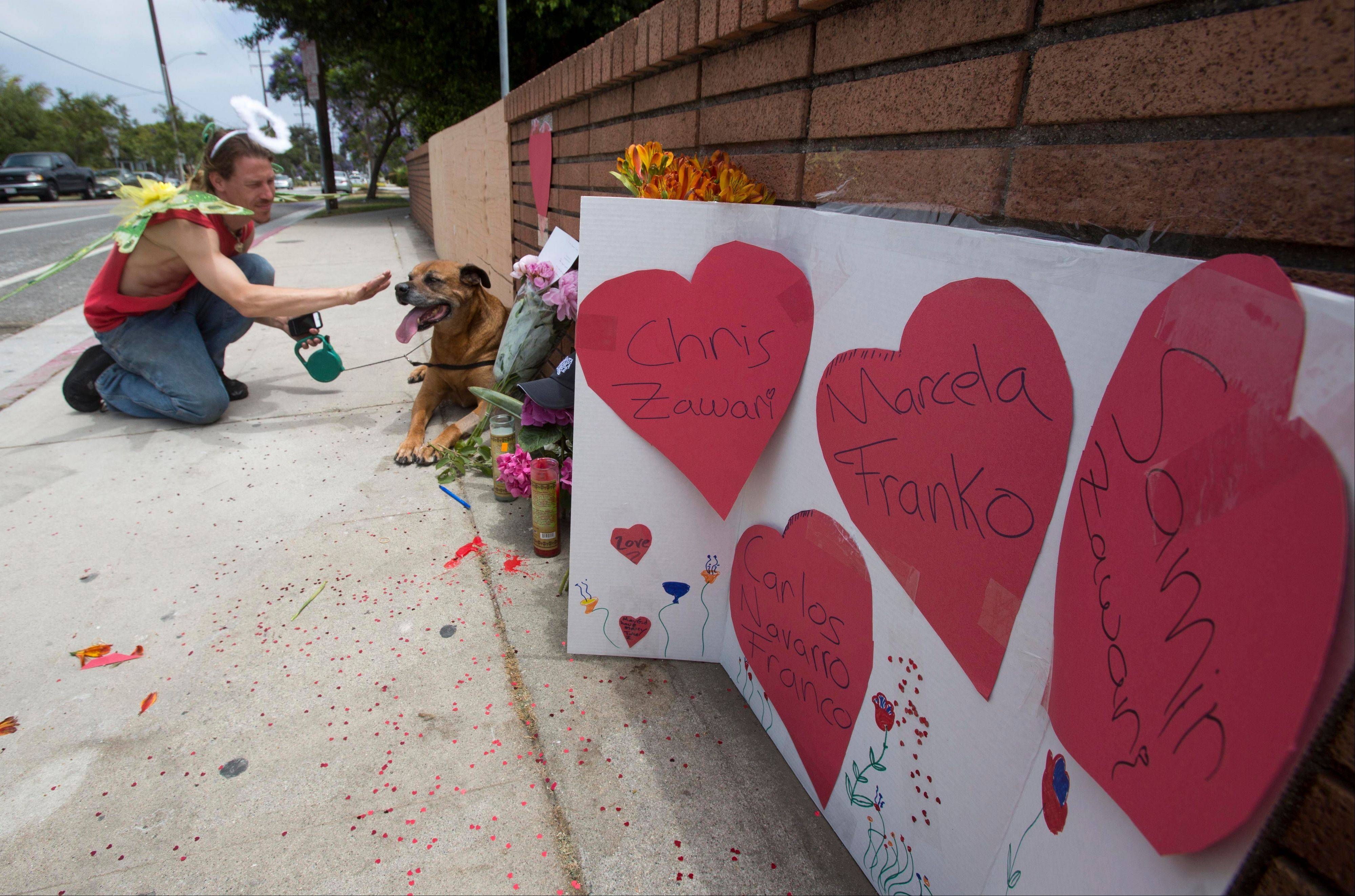 Nate Edelson, 39, a former student of Santa Monica College, dressed as a Fairly Angel, pets his dog Bull after putting heart-covered messages at a makeshift memorial at Santa Monica College Sunday in Santa Monica, Calif. A shooting rampage that resulted in six deaths ended at the campus on Friday.