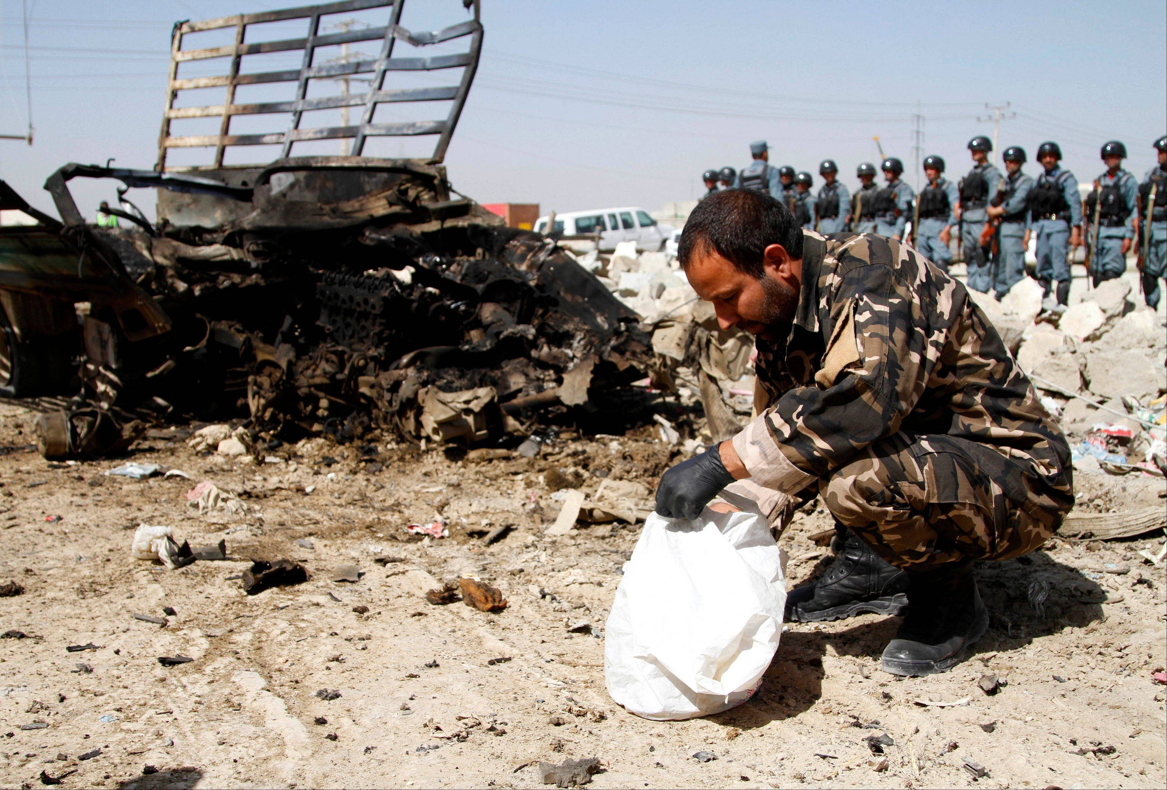Afghan security and intelligence official inspects wreckage at the site of a suicide attack near Kabul military airport in Kabul, Afghanistan, Monday. Seven heavily armed Taliban insurgents launched a pre-dawn attack near Afghanistan's main airport Monday, apparently targeting NATO's airport headquarters with rocket-propelled grenades, assault rifles and at least one large bomb. Two Afghan civilians were wounded and all the attackers were killed after an hours-long battle.
