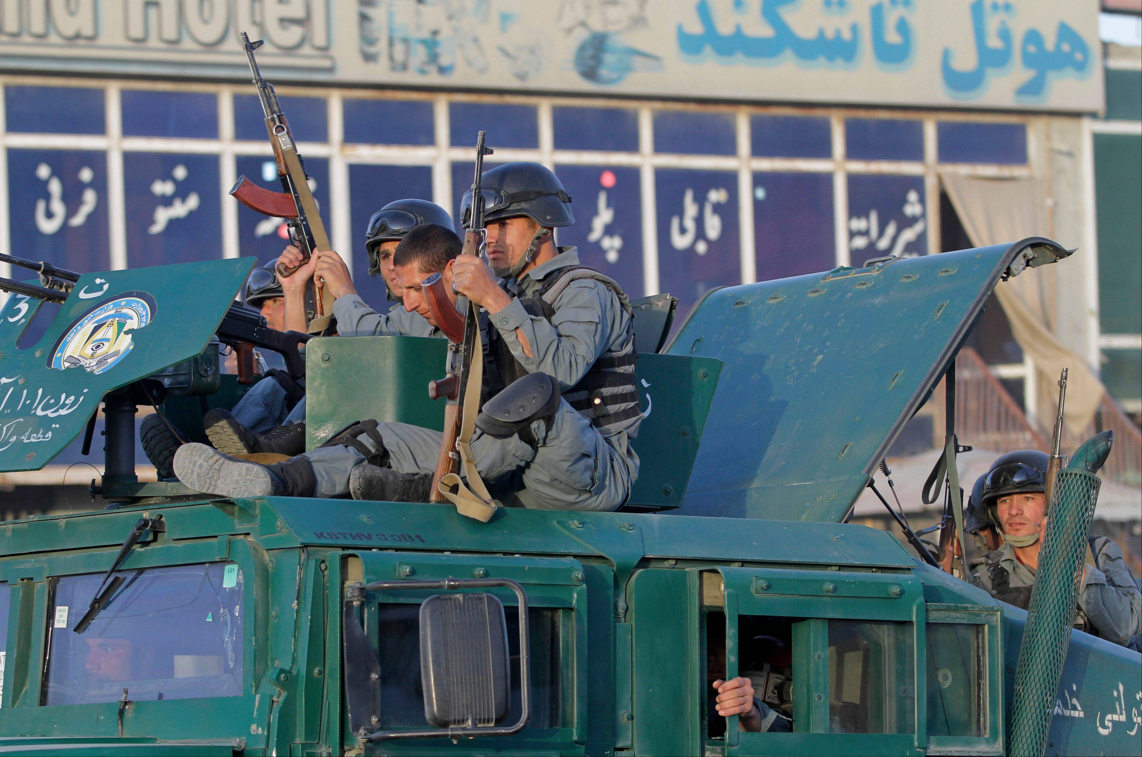 Afghan policemen sit atop a vehicle upon arrival after Taliban fighters attacked near Kabul airport, Afghanistan, Monday.