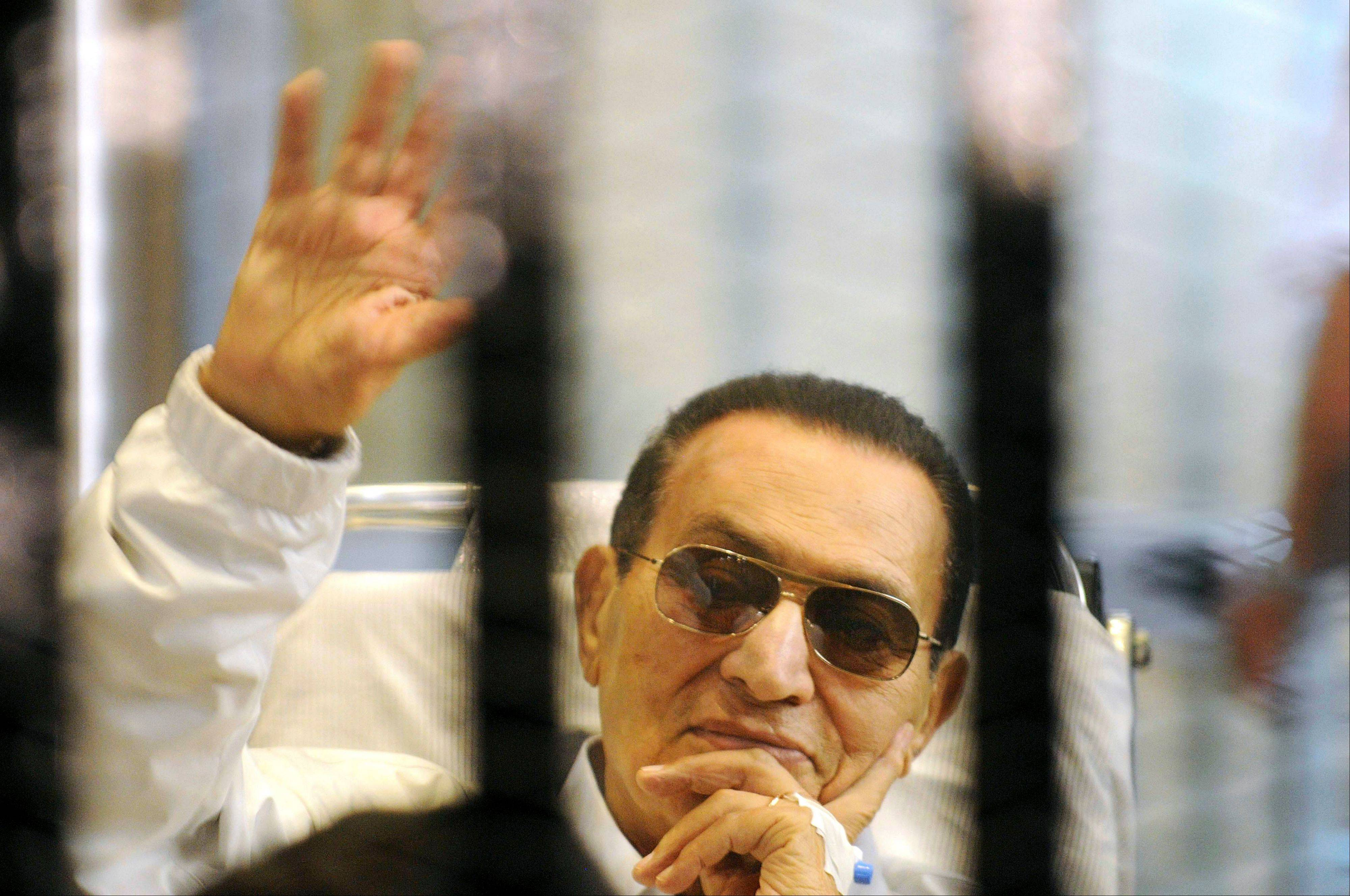 Former Egyptian President Hosni Mubarak waves to his supporters from behind bars as he attends a hearing in his retrial on appeal in Cairo, Egypt.