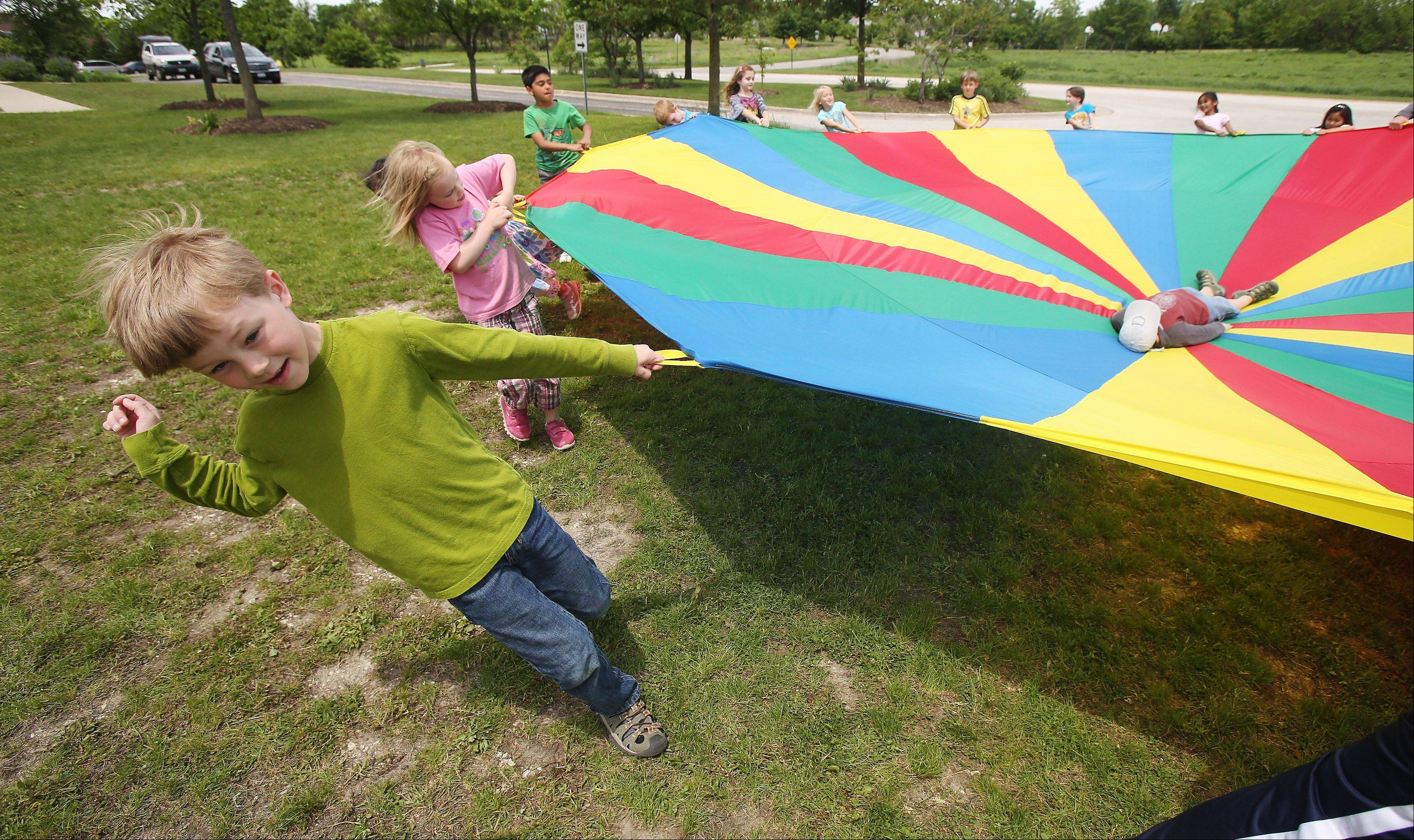 First graders Isaac Berski, left, and Mae Anderson, join classmates as they play with a parachute during Field Day Tuesday at Prairie Crossing Charter School in Grayslake.