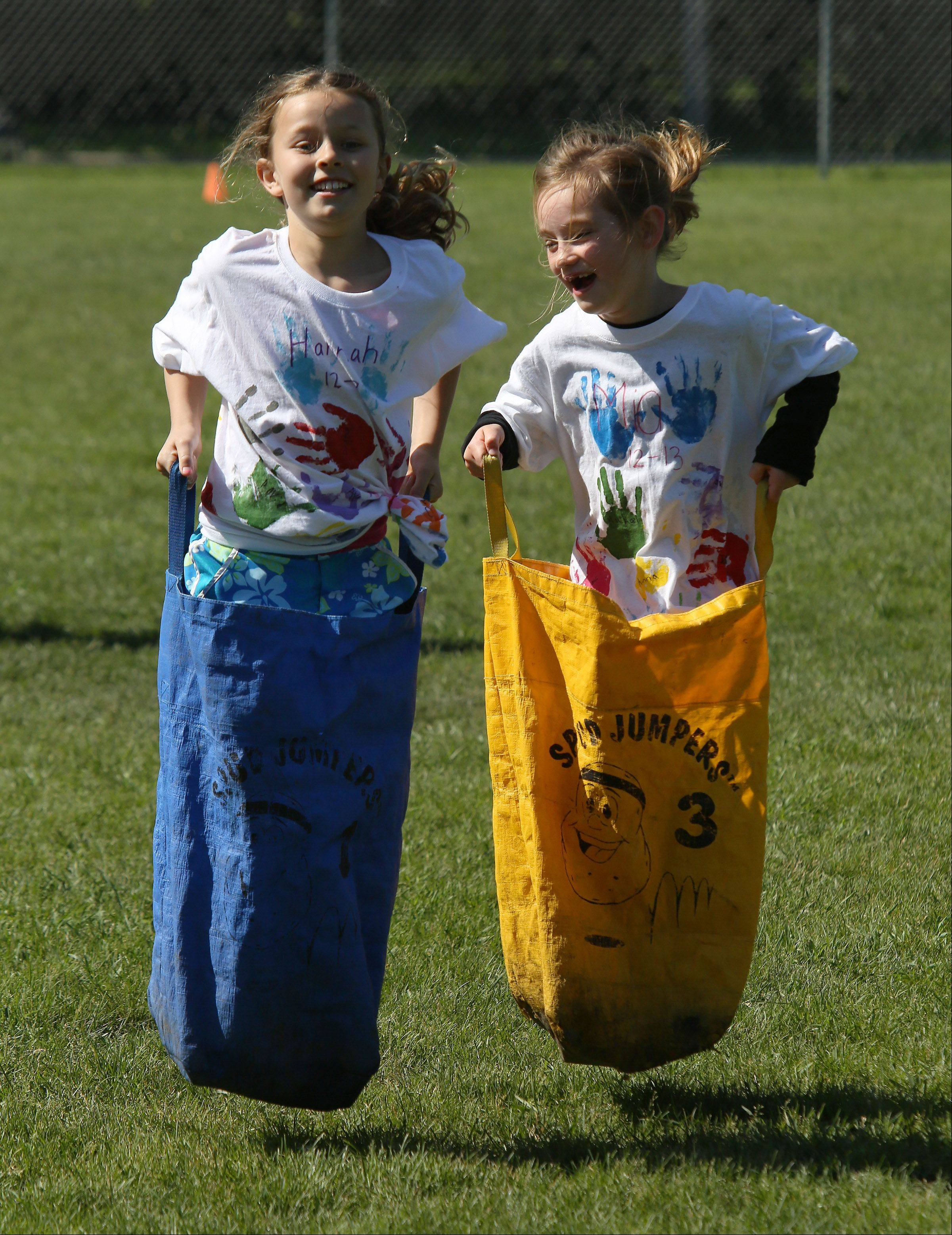 First graders Hannah Fleming, left, and Mia Colton, compete in the sack race during Field Day Monday at Rockland School in Libertyville. Students spent a beautiful spring day competing in field events and playing games.
