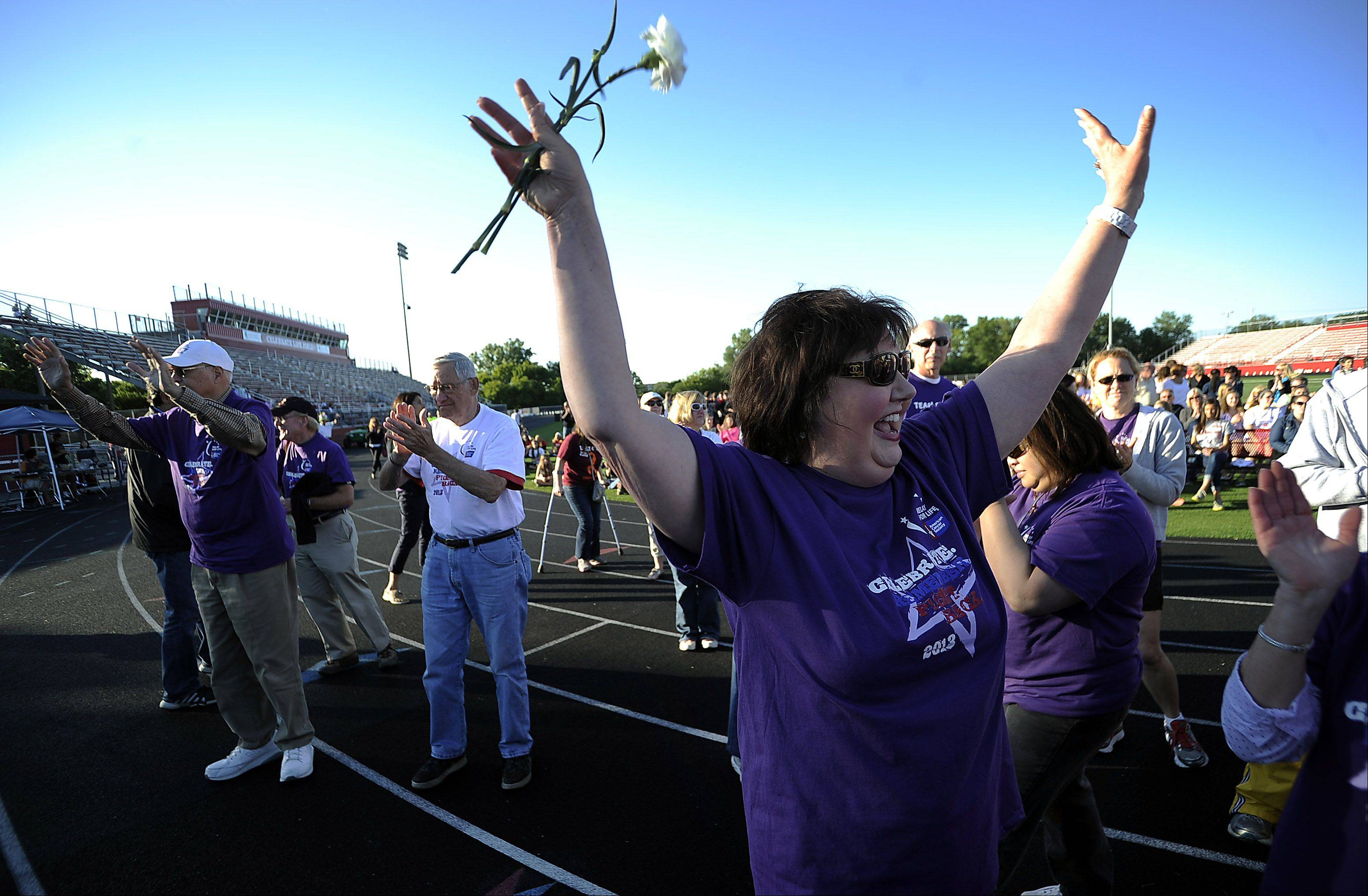 Wendy Goodman, of Crystal Lake, who is a 20-year survivor of cancer, celebrates life with others around her at Barrington's Relay For Life at Barrington High School Friday.