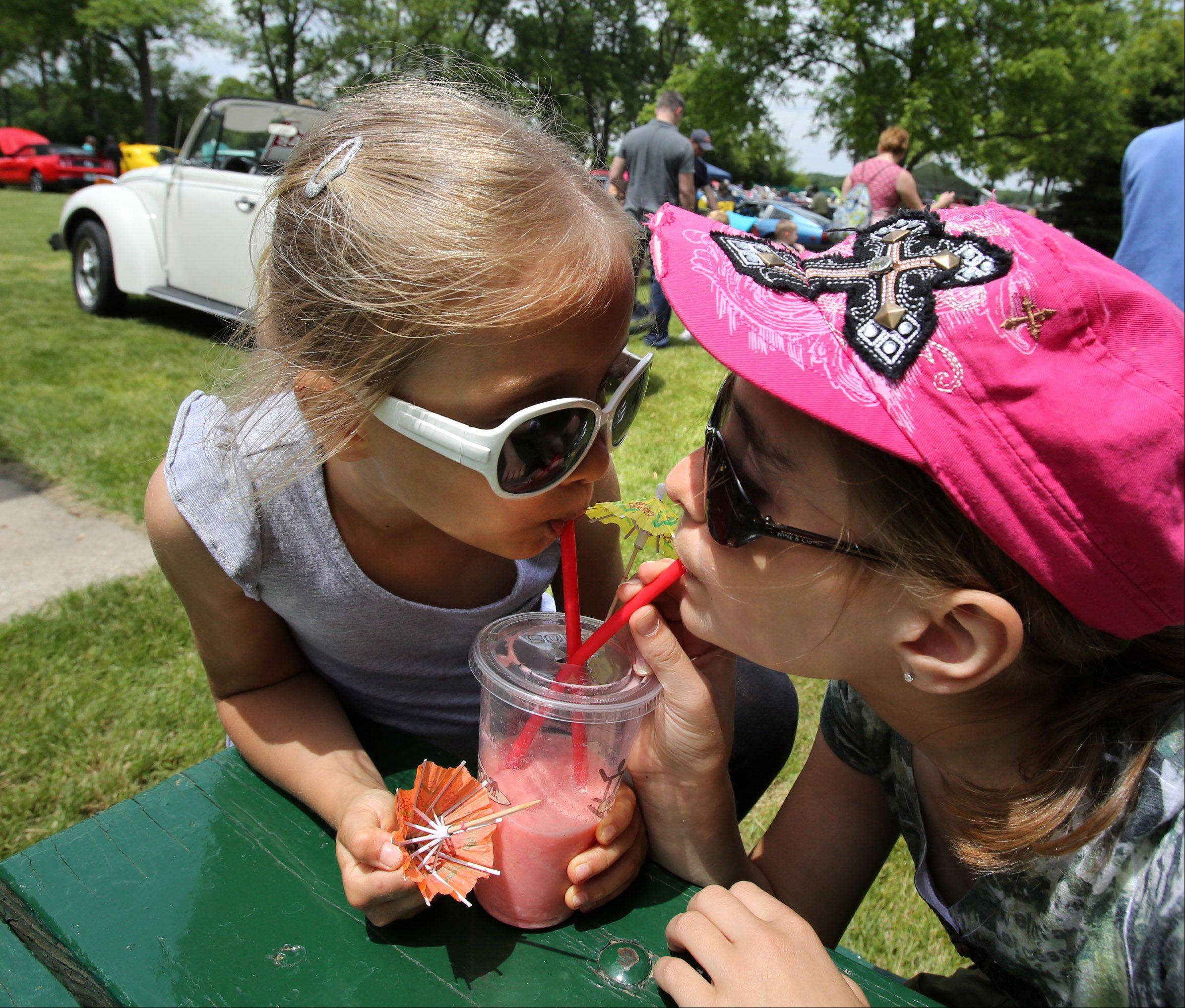 Sophia Frank, 6, and her sister Isabella, 11, both of Lake Villa, share a smoothie during the auto show at Lake Villa Celebration of Summer at Lehmann Park in Lake Villa Saturday.
