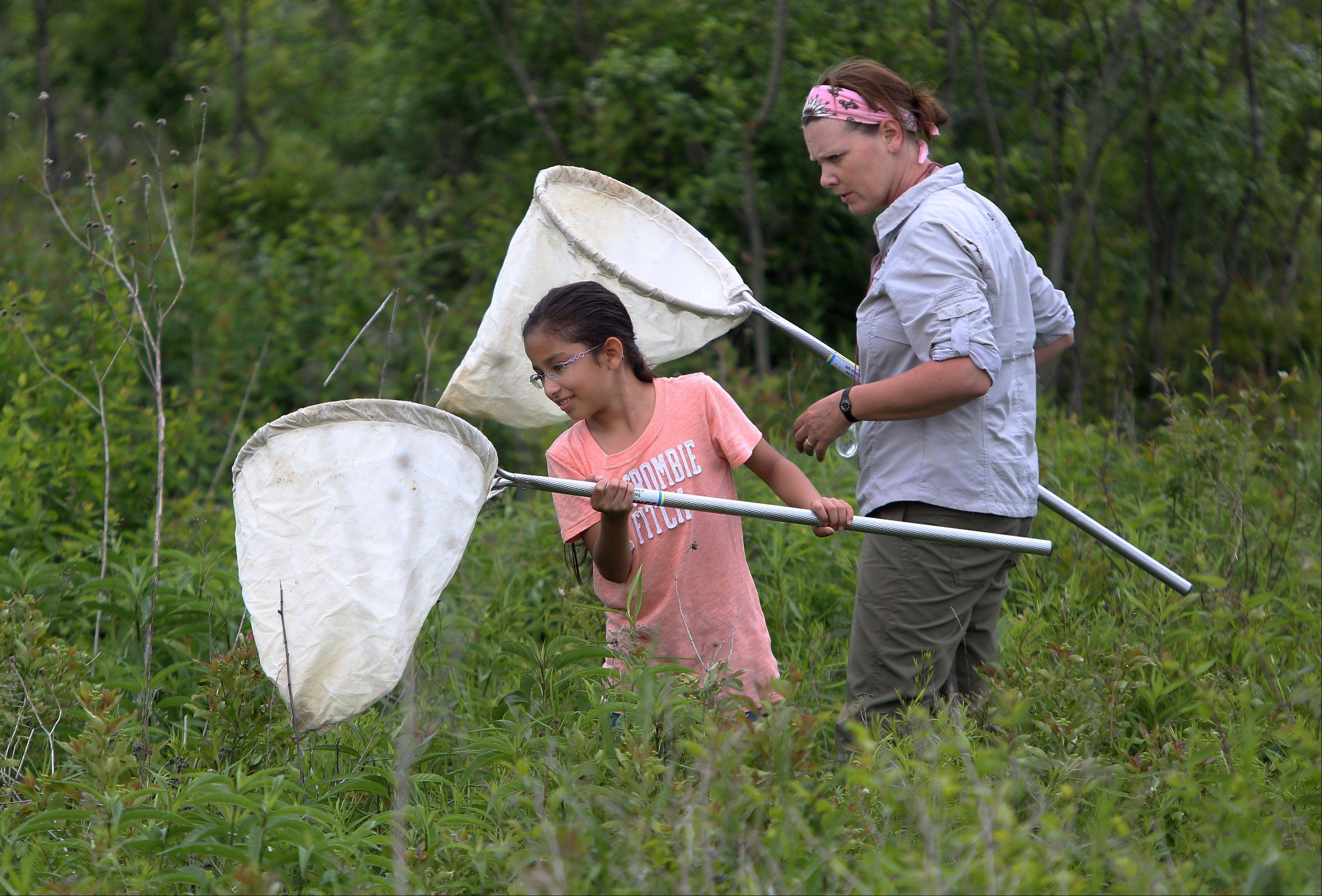 Brianna Ruiz, 9, of Waukegan, collects bugs with environmental educator Christine Blakely during Lake County Forest Preserve's Kids Nature Funfest Sunday at the Greenbelt Cultural Center in North Chicago. Kids ages 4-12 explored nature with hands-on activities and fun games.