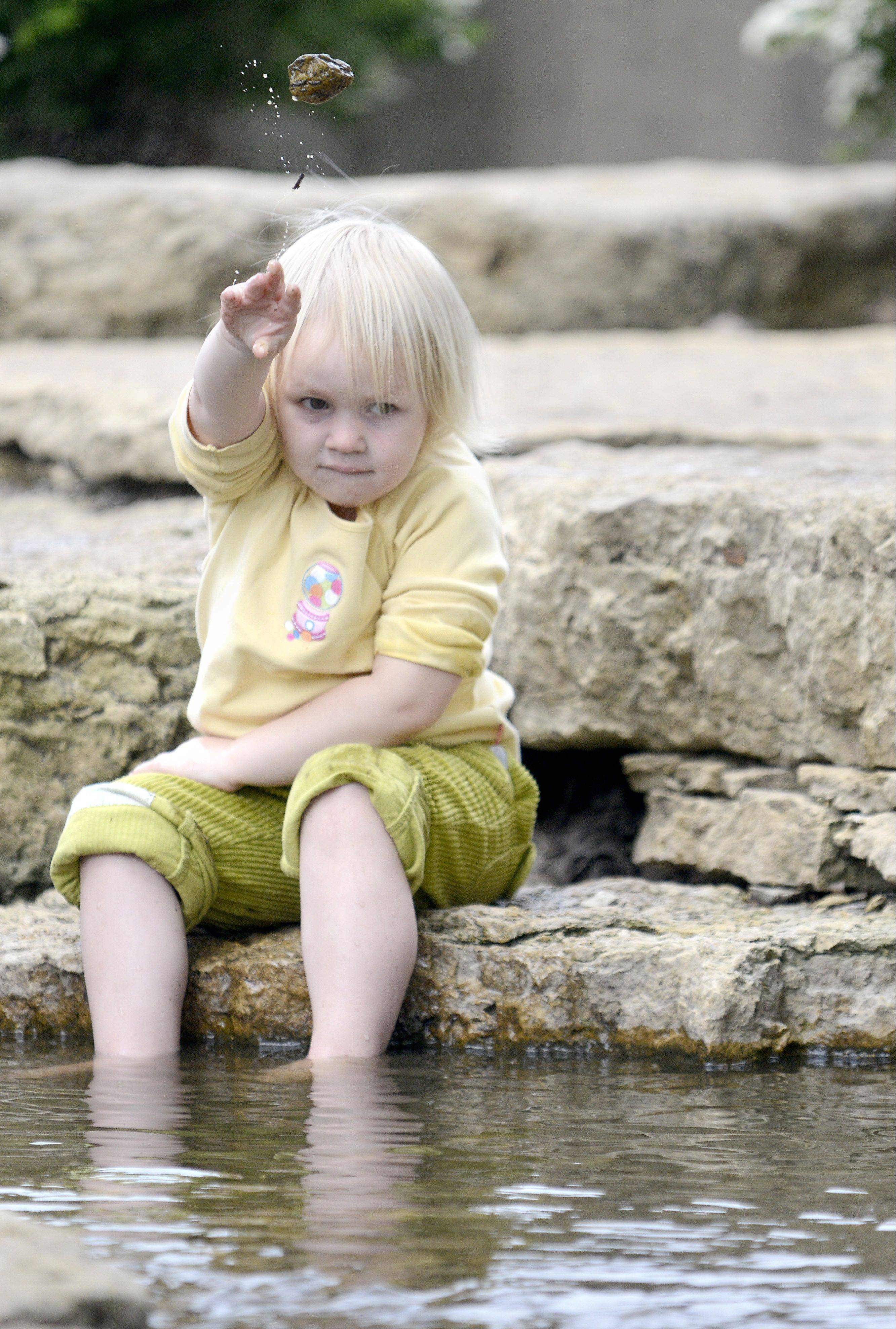 "While dipping her toes in the cool water, Eliza Bruhl, 2, of Elburn tosses rocks in a stream by the Riverwalk at Pottwatomie Park in St. Charles Tuesday. Eliza, along with her sister, Lillian, 6, brothers Acelin, 9, Aidan, 7, and friend, Eloise Cole, 8, all of Elburn, spent the day ""park hopping"" in St. Charles with Eloise's mom, Kim. ""[It was] Just too nice of a day to spend inside,"" said Kim Cole."